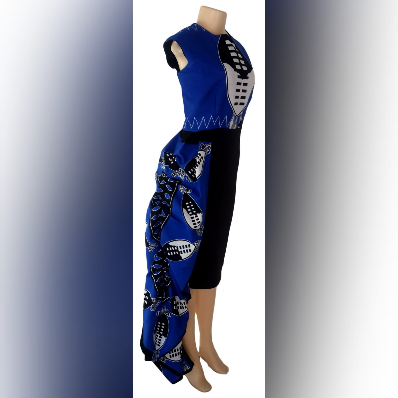 Blue swati knee length dress with hip frill 4 modern traditional knee-length fitted swati dress in blue, black and white. With a hip frill. With matching black golf shirt detailed with swati fabric. Traditional wedding attire.