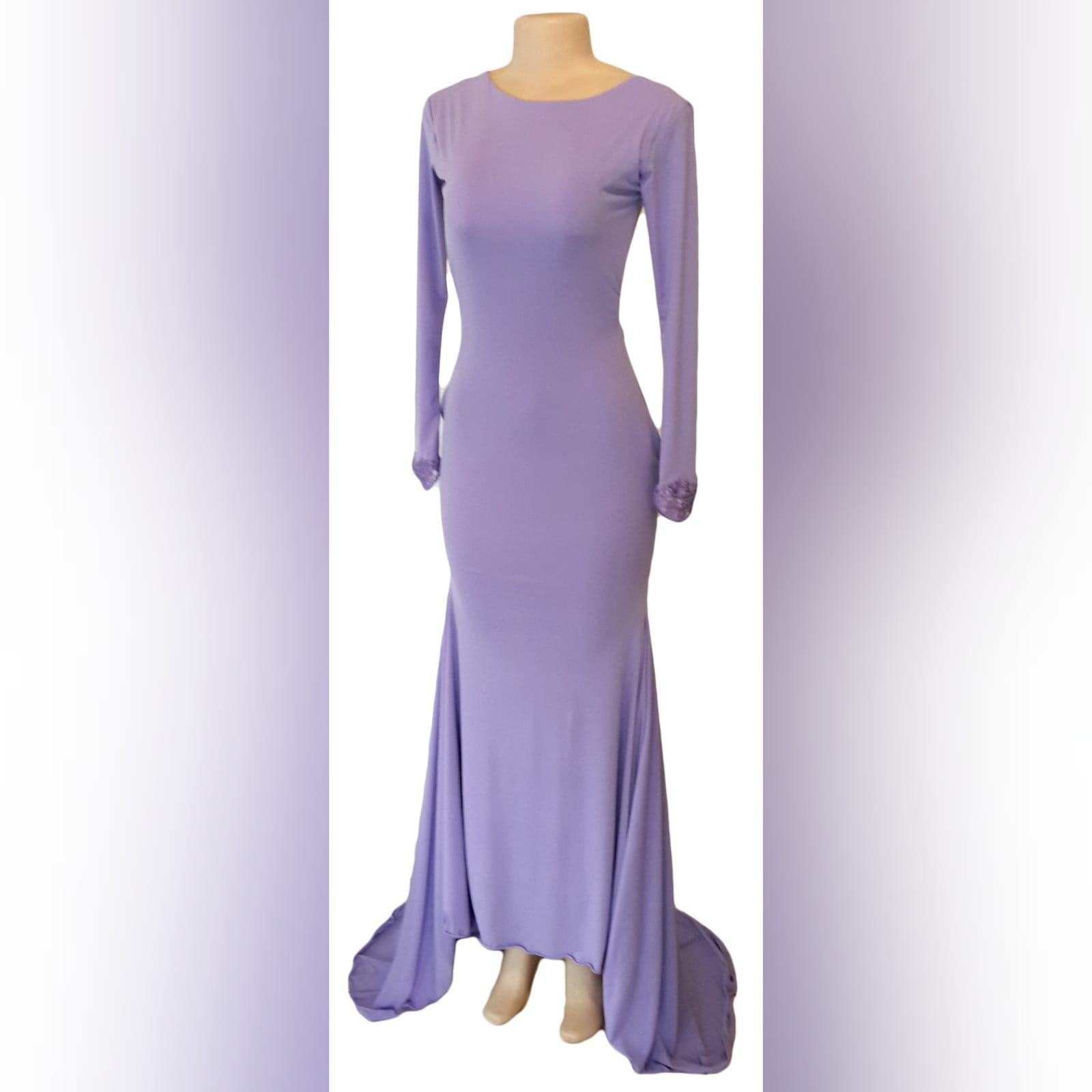 Body fitting lilac soft mermaid prom dress and a jewel neckline 4 body fitting lilac soft memaid prom dress and a jewel neckline. Low open square back. With a train and long sleeves. Sleeves finished with lace.