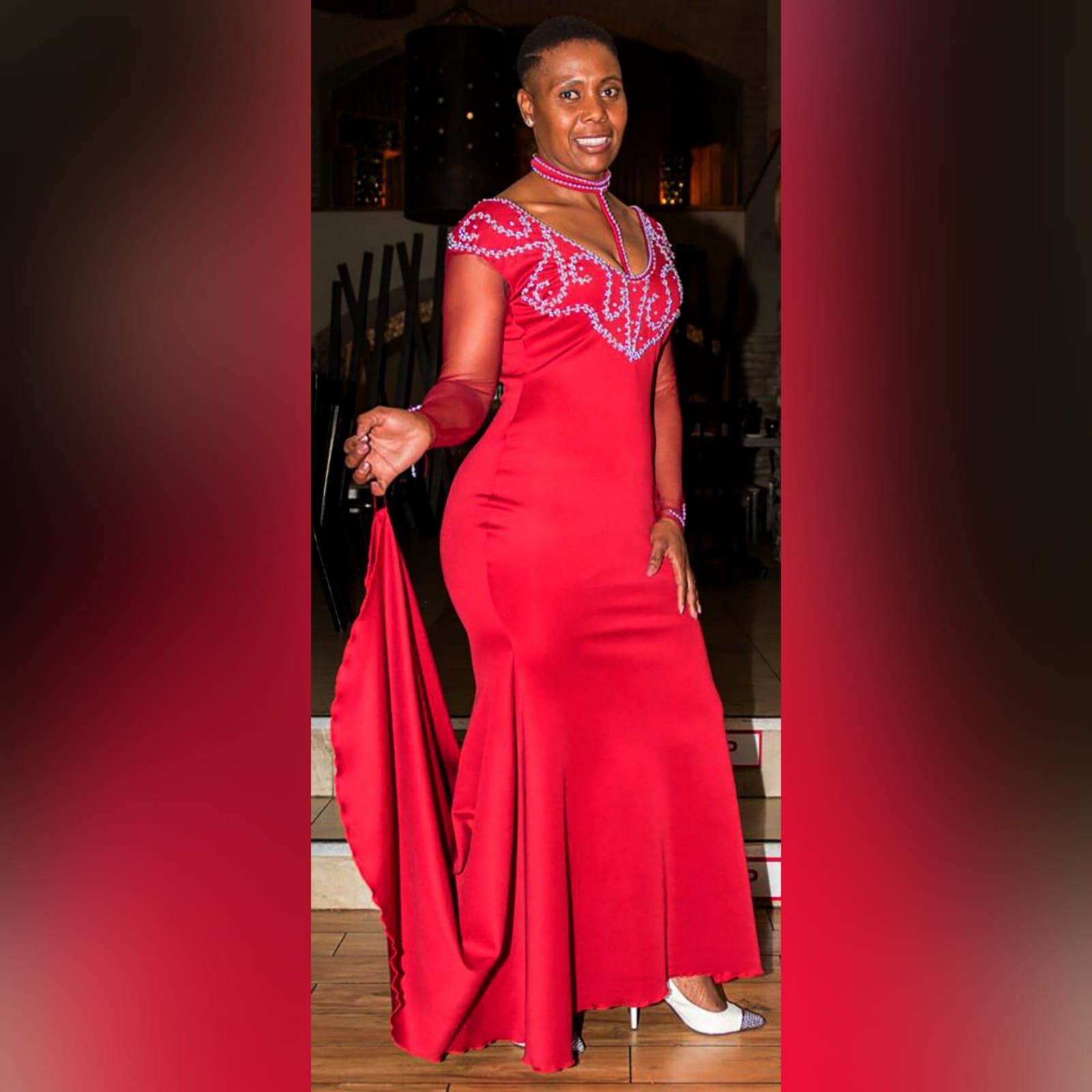Beaded red long evening party dress 1 red long evening party dress, fitted till hip then it flares out a bit, with a train, with long sheer sleeves. Dress with a v neckline detailed in silver with an optional choker.