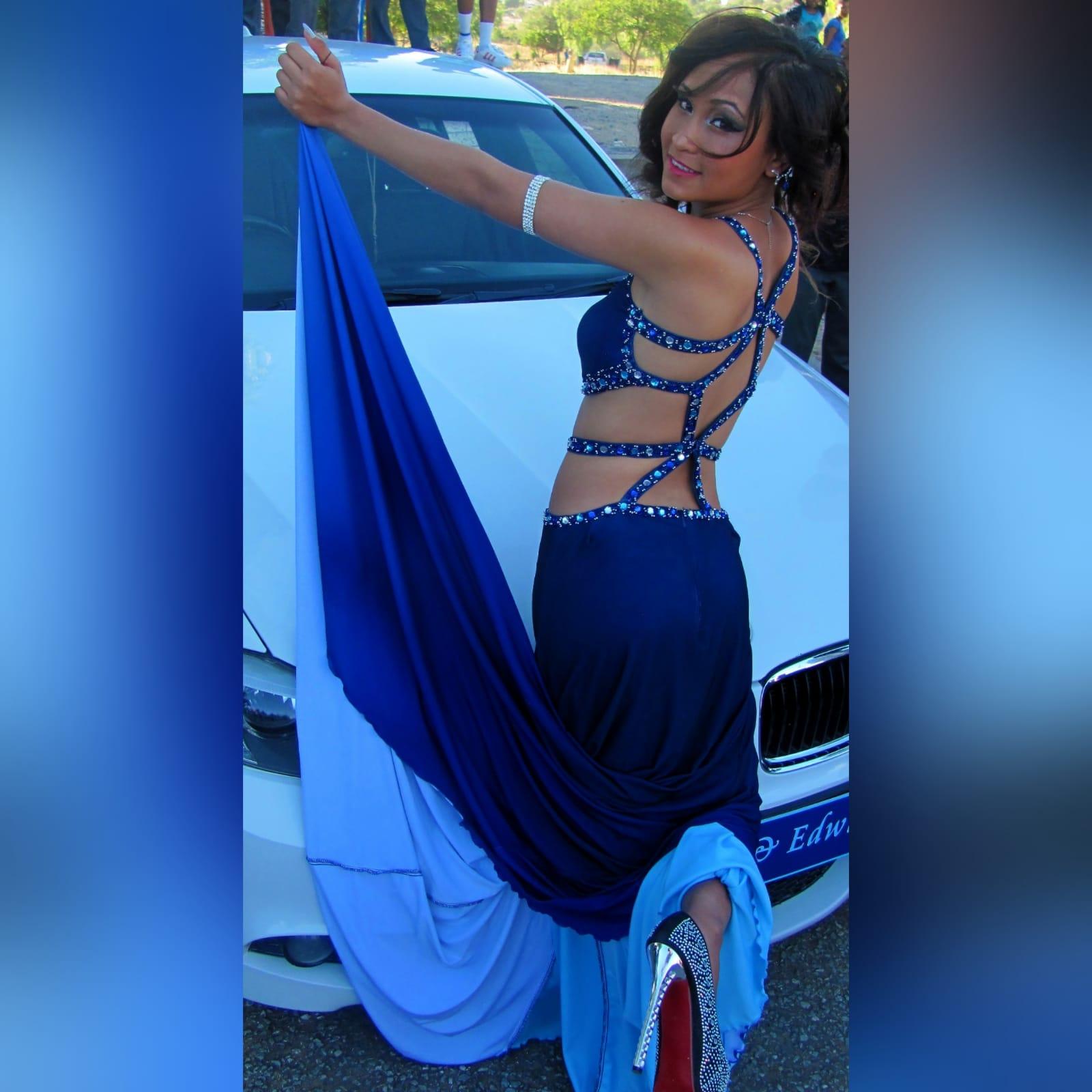 Vestido de finalista sexy azul com pedras 2 vestido de finalista sexy azul com pedras. Com uma racha e uma cauda. Com aberturas na barriga e nas costas detalhadas com pedras prateadas, azuis e turquesa. Vestido com vários tons de azul.