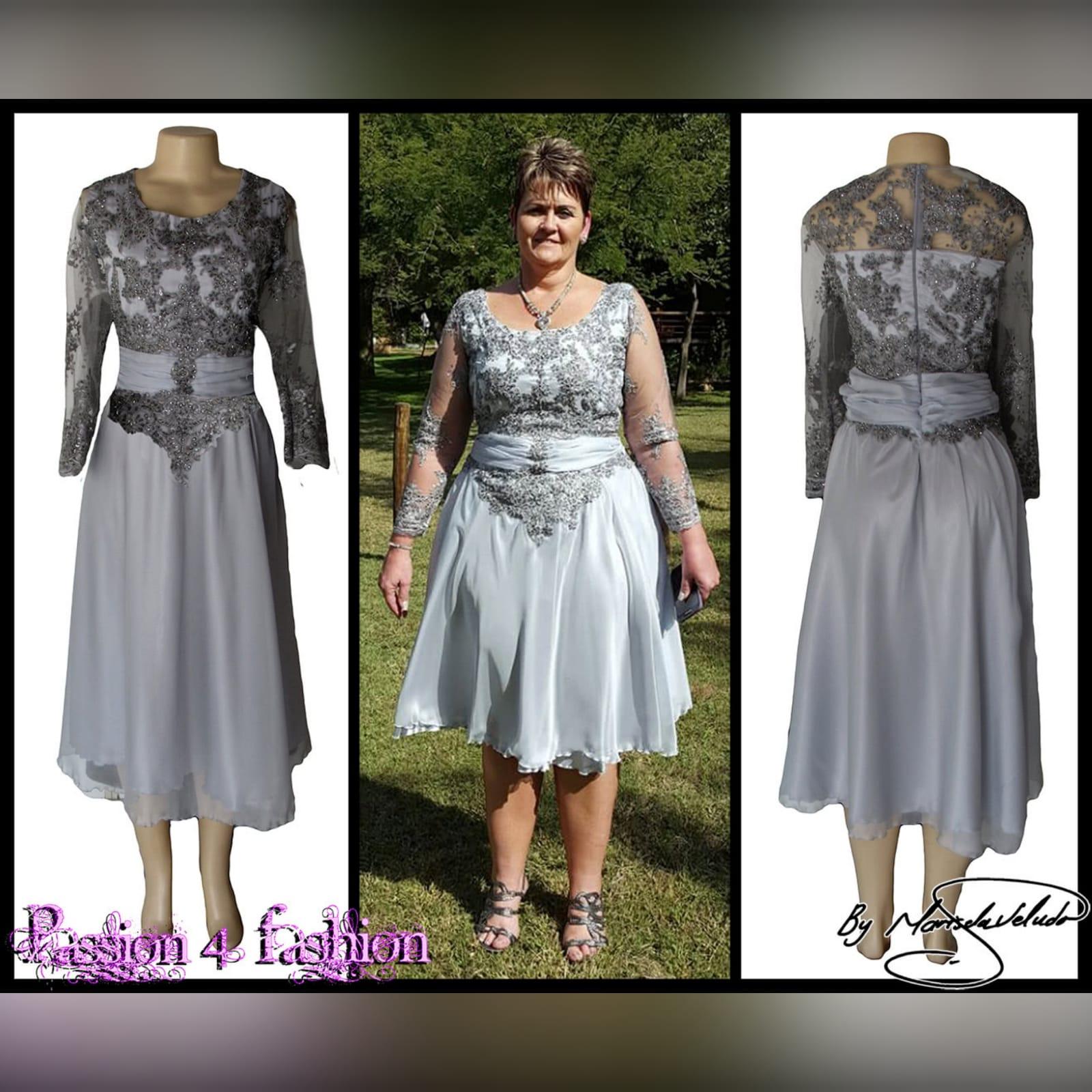 Vestido curto mãe da noiva cinzento 4 vestido da mãe da noiva comprimento de joelho cor cinza. Detalhado com um cinto reunido e rendas no corpete e mangas.