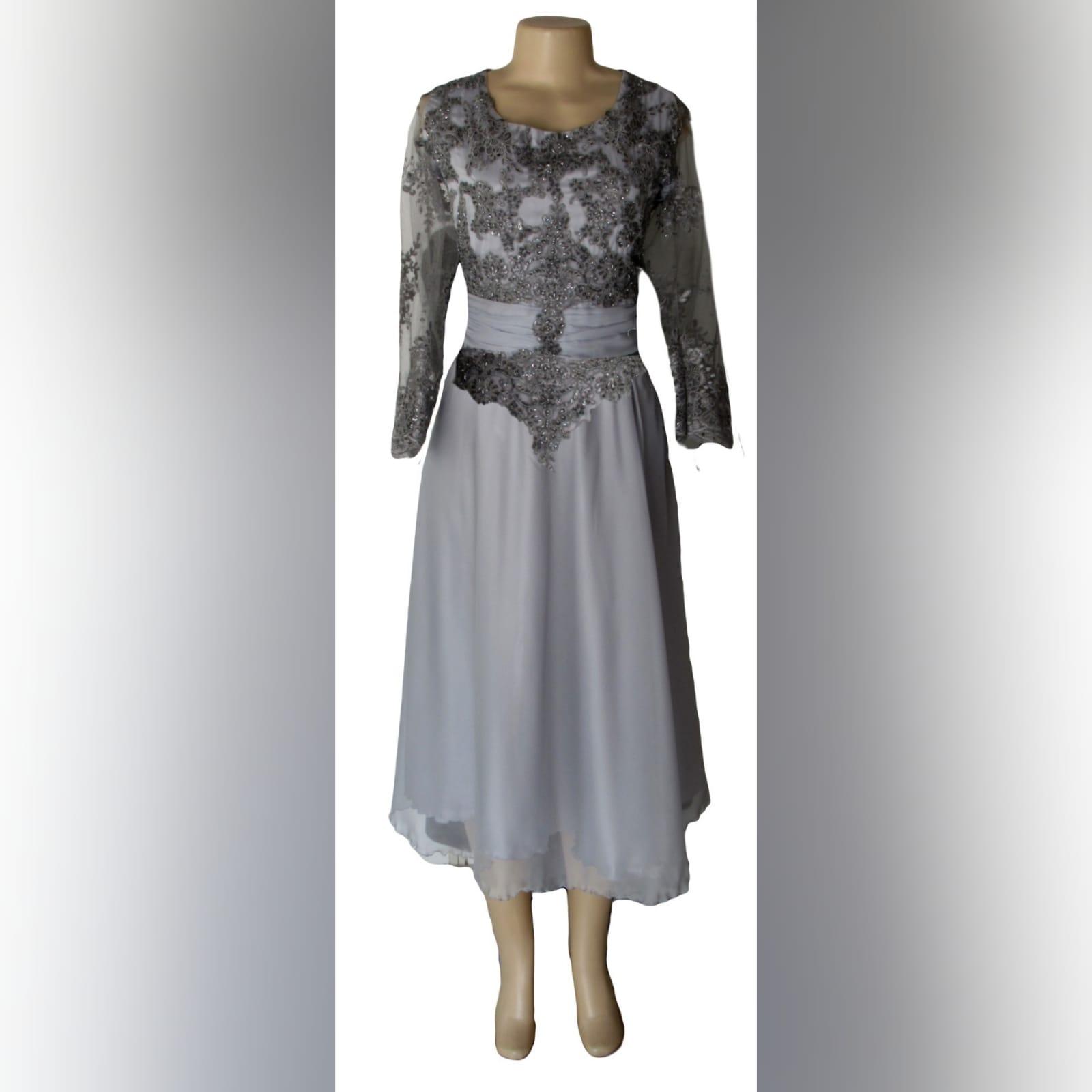 Vestido curto mãe da noiva cinzento 6 vestido da mãe da noiva comprimento de joelho cor cinza. Detalhado com um cinto reunido e rendas no corpete e mangas.