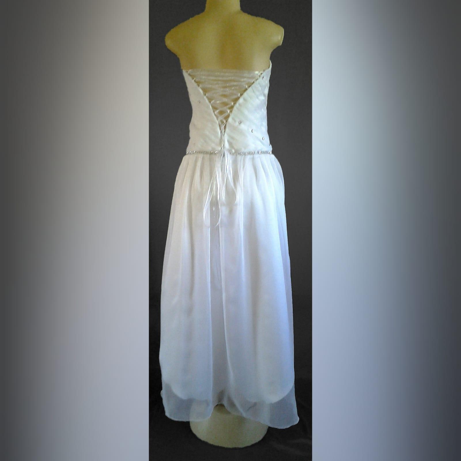 Hi-lo pleated bodice white wedding dress 2 hi-lo white chiffon wedding dress with a full pleated bodice. This wedding dress has a lace up back and silver finishes.