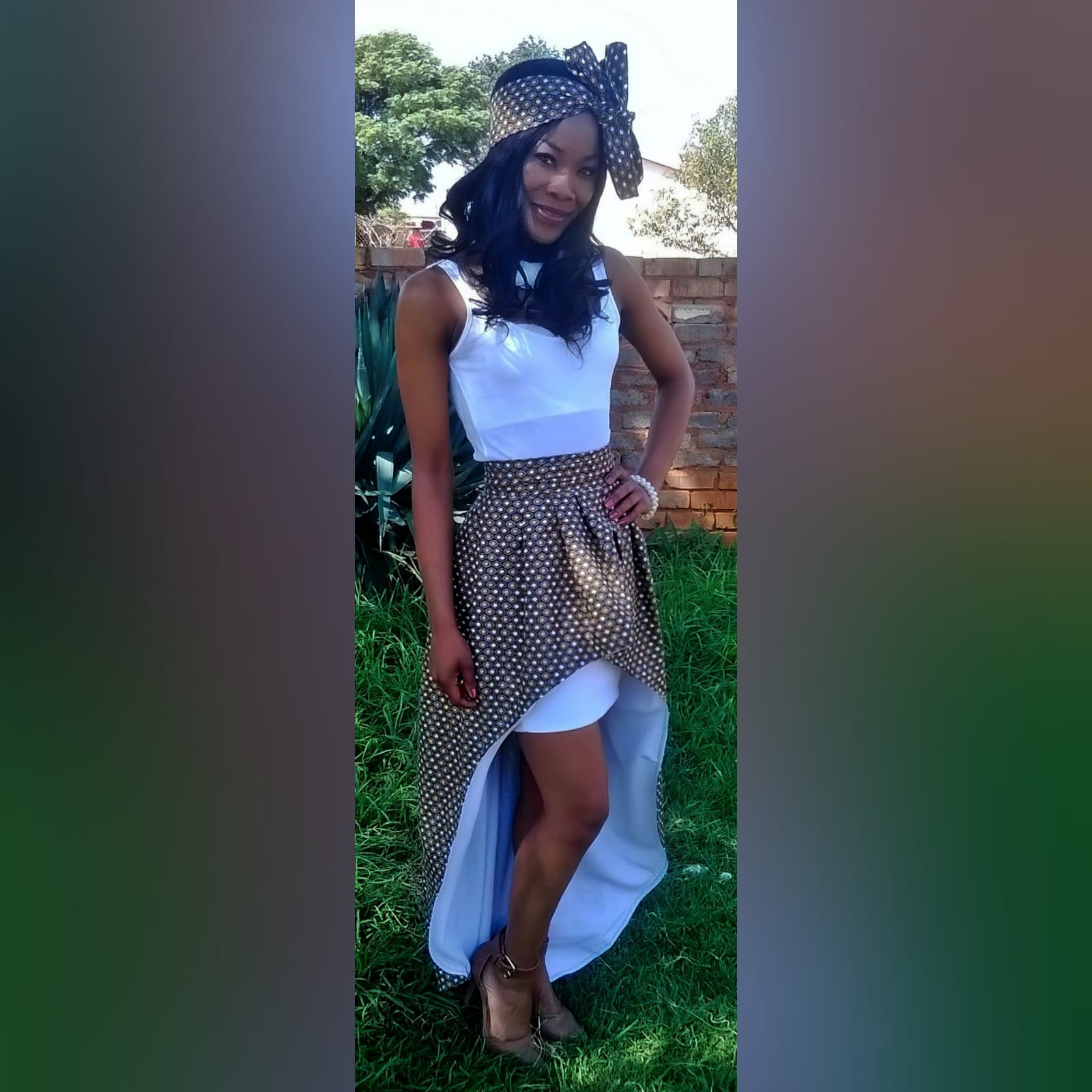 High waisted hi-low traditional skirt with xhosa print 1 high waisted 2 in 1 high low traditional skirt with xhosa print. Inside of the high low lined with white. With an attached mini white skirt. Matching doek.