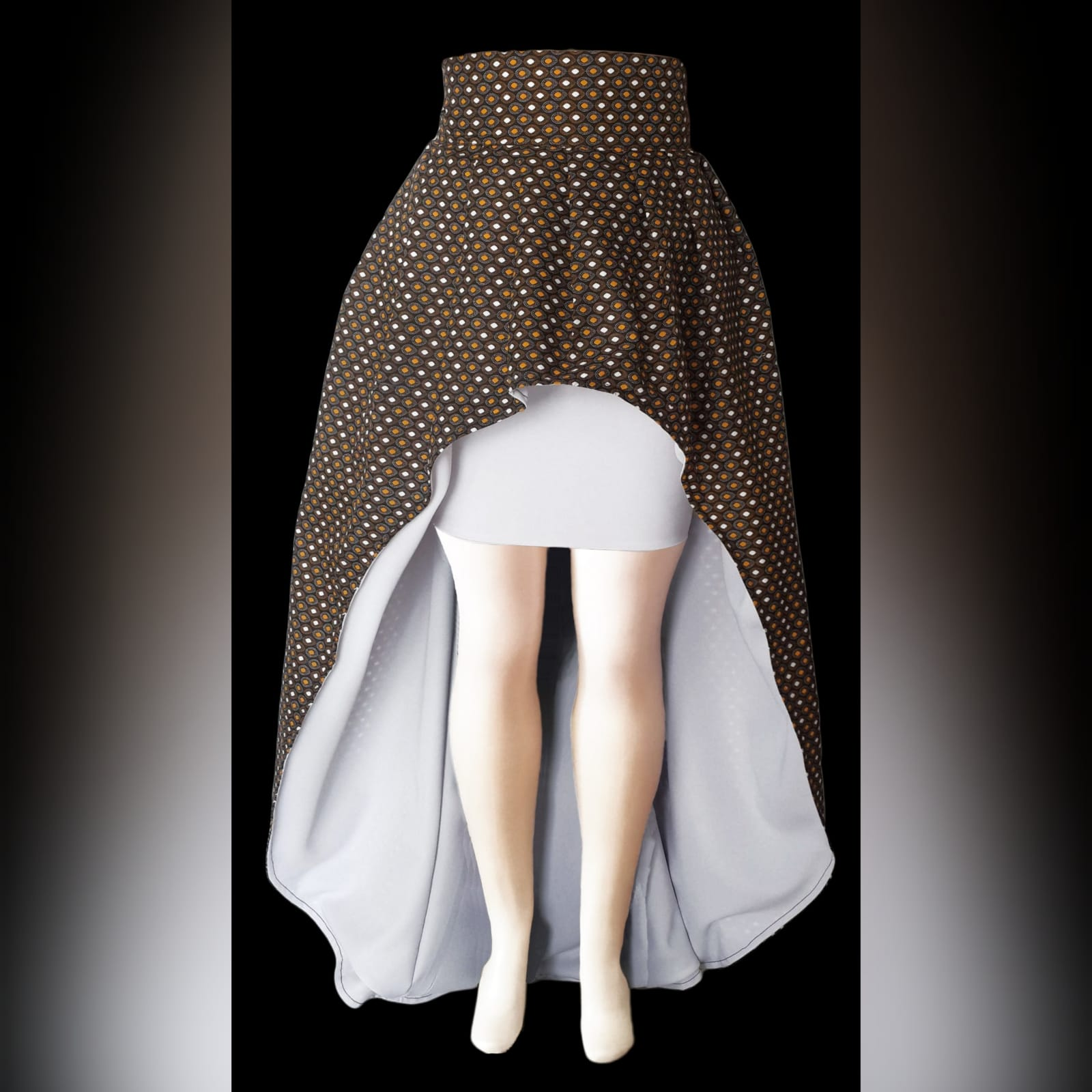 High waisted hi-low traditional skirt with xhosa print 3 high waisted 2 in 1 high low traditional skirt with xhosa print. Inside of the high low lined with white. With an attached mini white skirt. Matching doek.