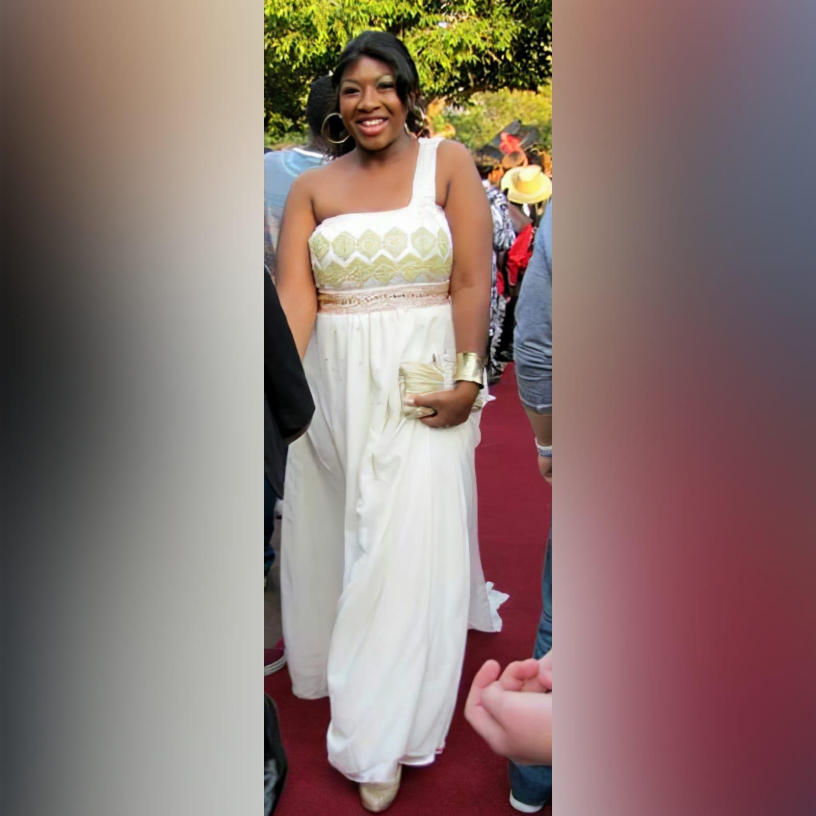 Vestido de finalistas cor pérola estilo deusa 1 vestido de finalistas cor pérola estilo deusa, corpete detalhado em enfeites de renda verde-oliva com brilhantes e pedras de ouro e bronze, com uma alça de um ombro com uma cauda de ombro anexado.