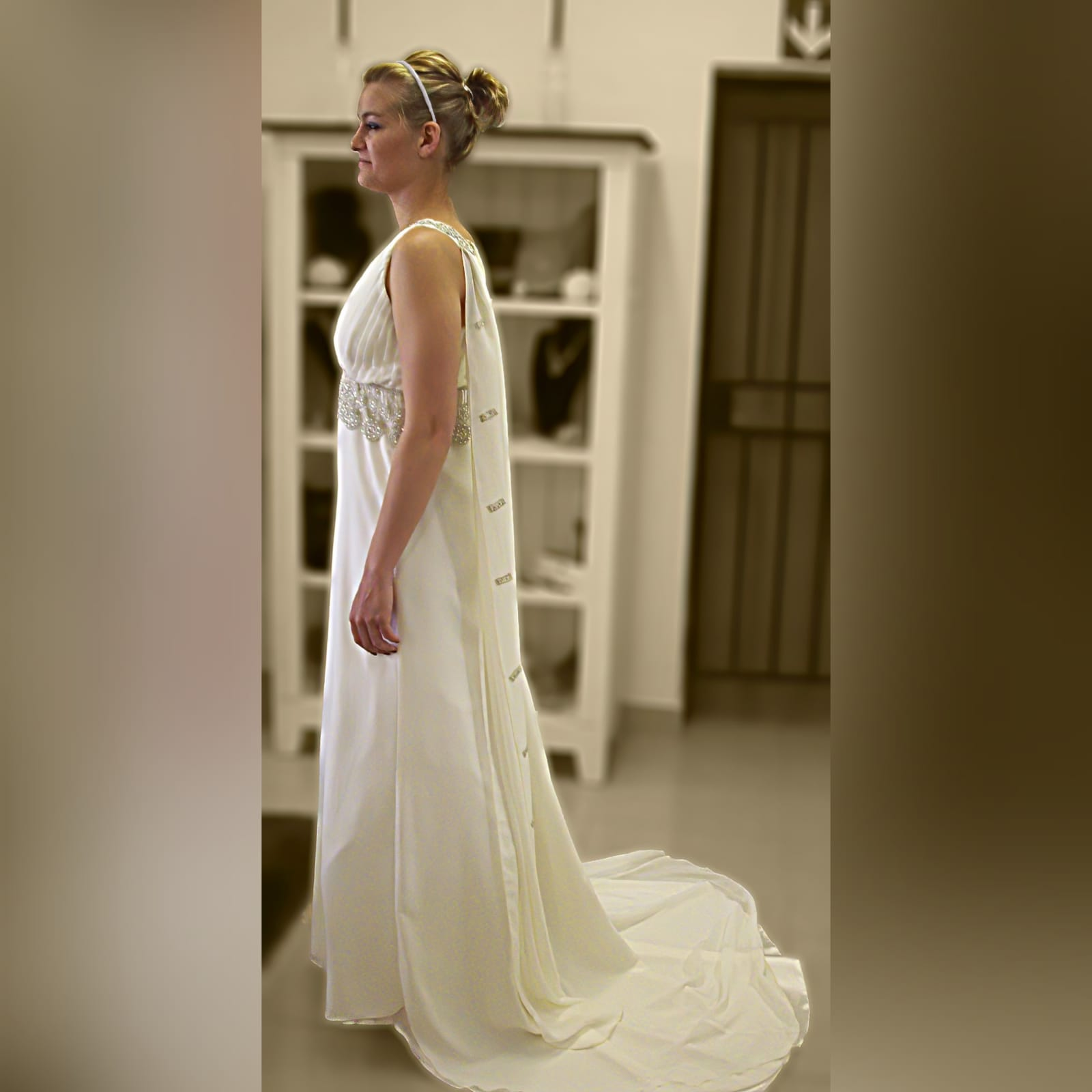 Ivory cross busted wedding dress with train 3 ivory cross busted wedding dress with an added back panel creating a train. Two long shoulder chiffon pieces decorated with bronze embroidery detail and under bust finish this wedding dress off.