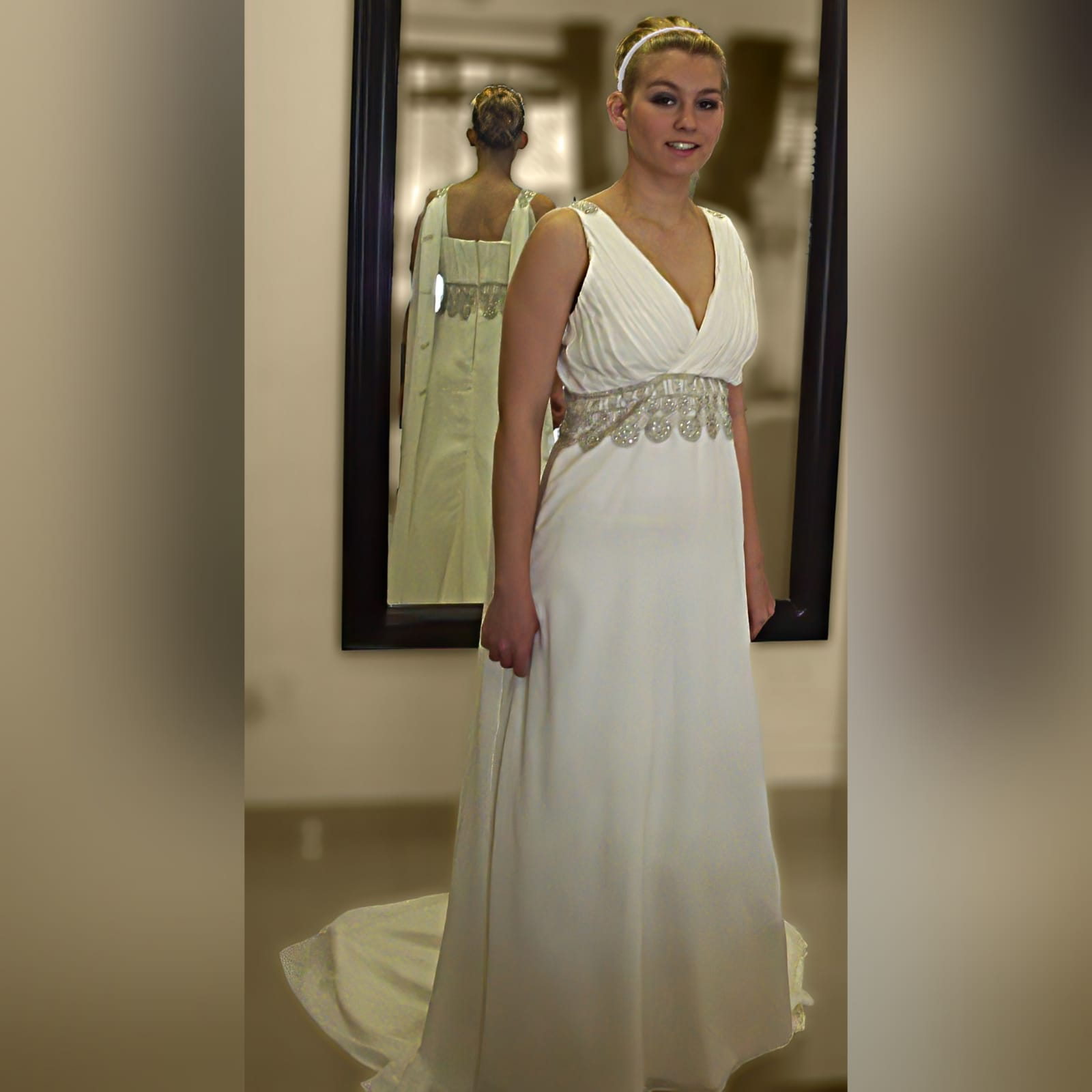 Ivory cross busted wedding dress with train 1 ivory cross busted wedding dress with an added back panel creating a train. Two long shoulder chiffon pieces decorated with bronze embroidery detail and under bust finish this wedding dress off.