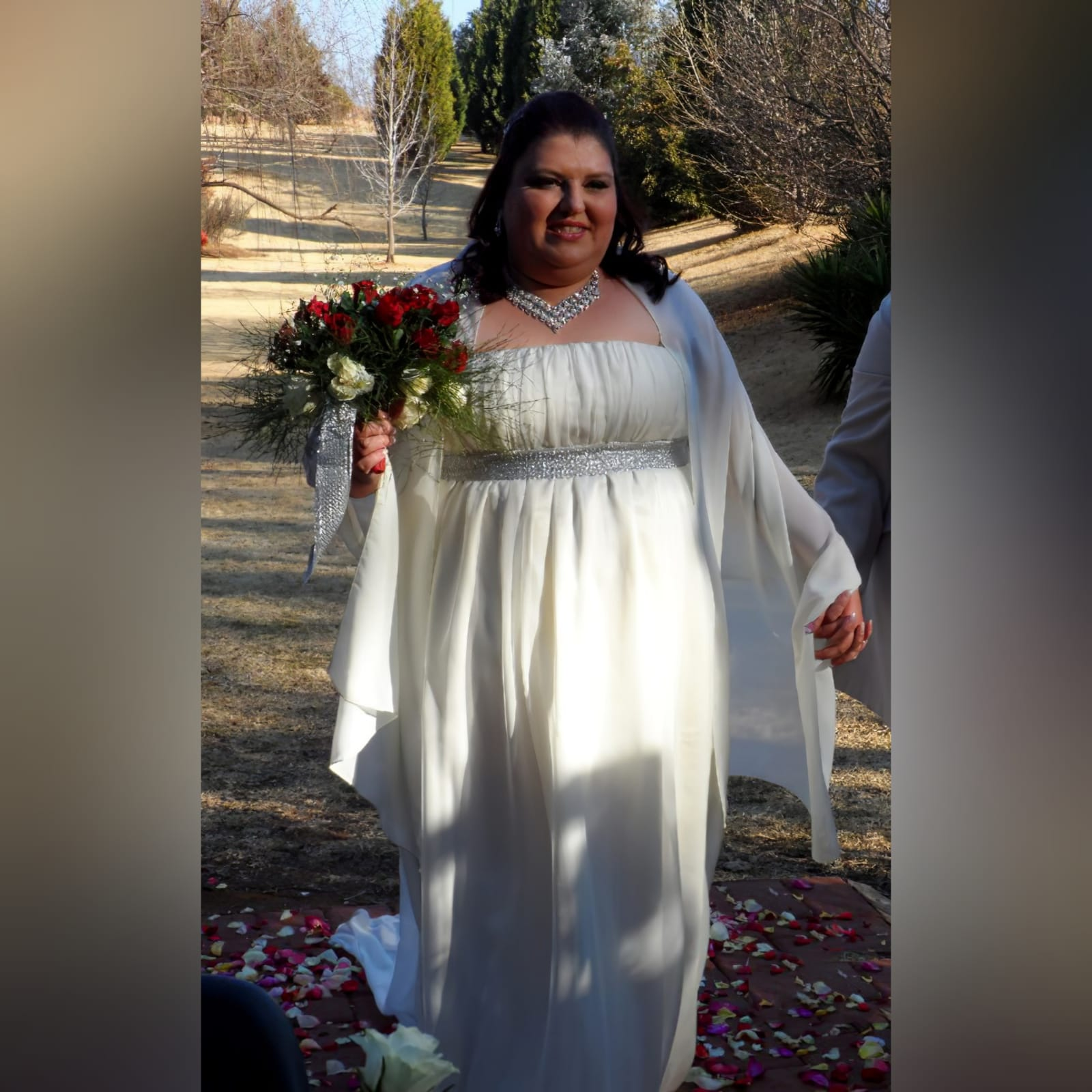 Ivory empire fit flowy plus size wedding dress 1 an ivory, empire fit flowy plus size wedding dress with a pleated straight, boob tube bust line. An ivory chiffon train and bust line silver detail finish this wedding dress. A shoulder chiffon shawl compliments the bride and the grooms shirt made by marisela veludo too.