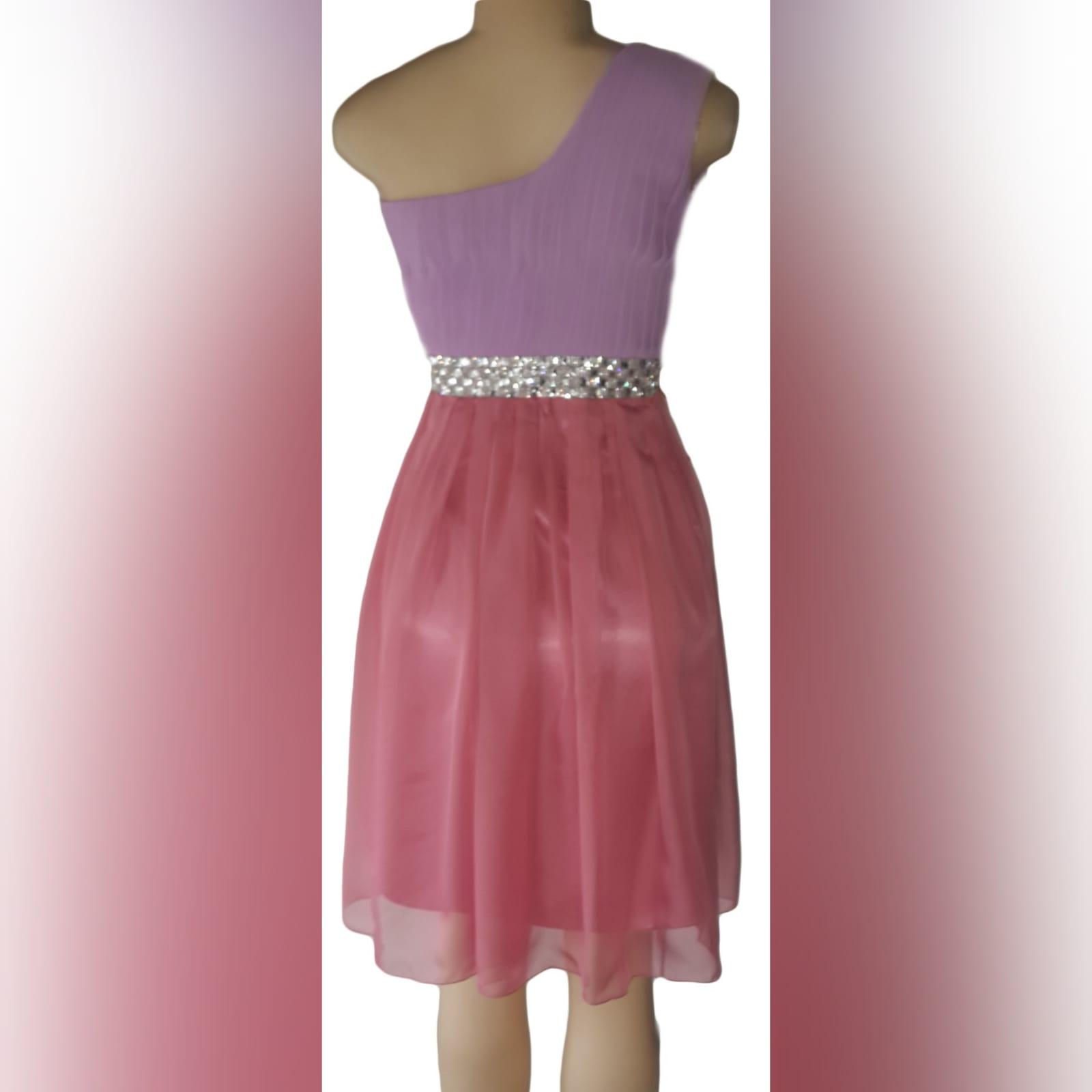Vestido curto de dama de honra cor-de-rosa e lilás 4 vestido curto de dama de honra em chiffon cor-de-rosa e lilás, com um só ombro. Corpete plissado com detalhe de cinturão prateado.