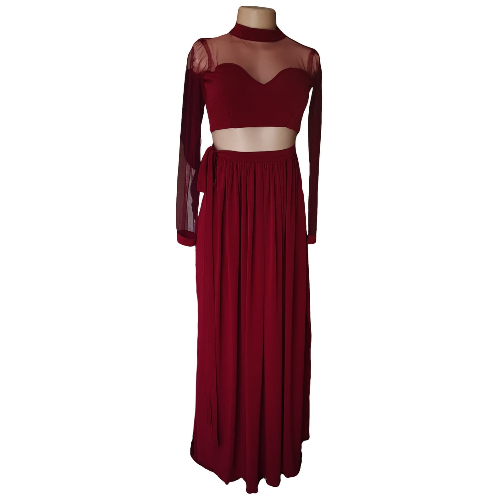 Maroon 2 piece long prom dress with a gathered skirt 4 maroon 2 piece long prom dress with a gathered skirt. With a slit and belt with tie up bow detail. Crop top, sheer sleeves and neckline creating a choker.