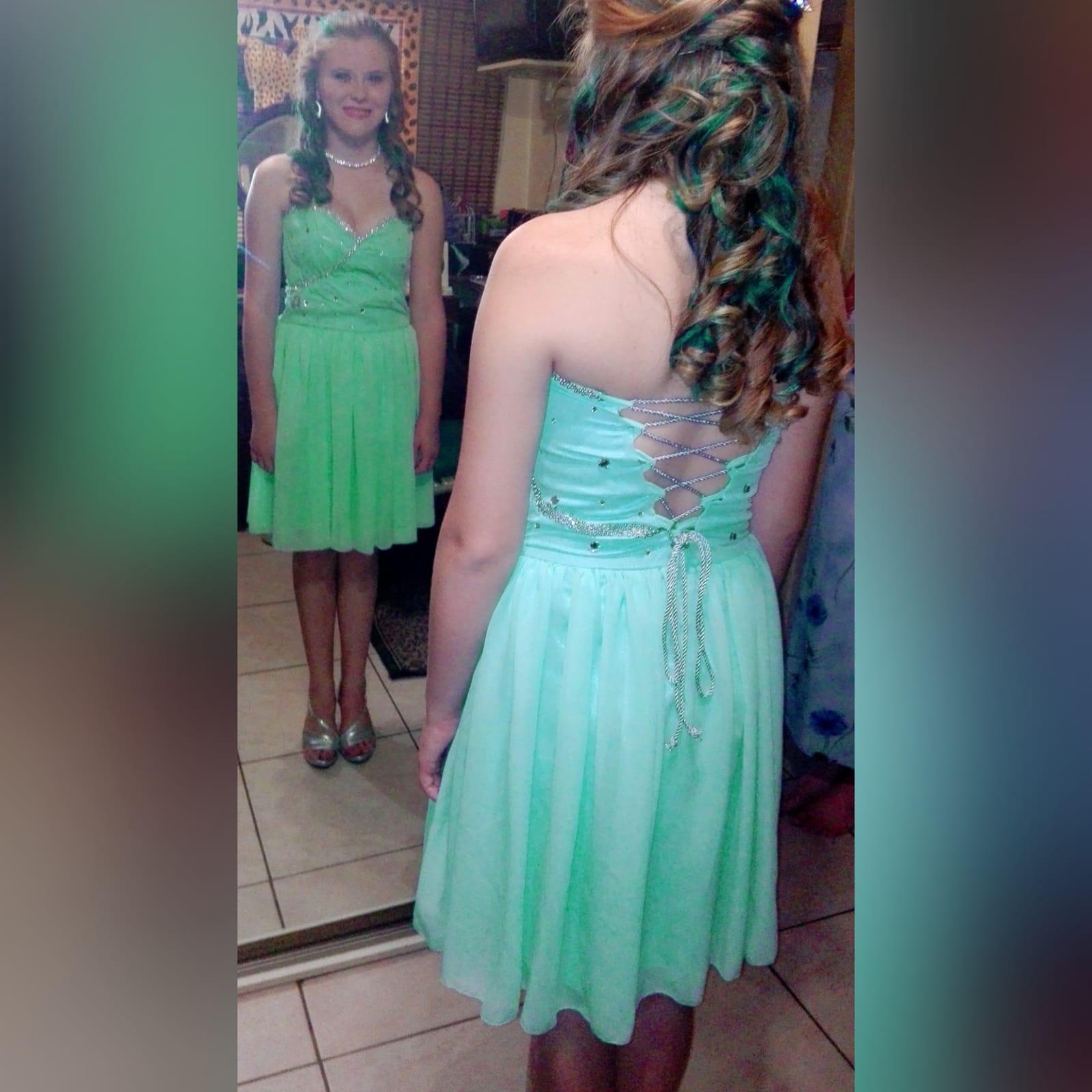 Vestido curto de finalistas cor verde menta 2 vestido curto de finalistas cor verde menta, sem ombros, com corpete decorado com pedras brilhantes cor prata. Com costas atadas.