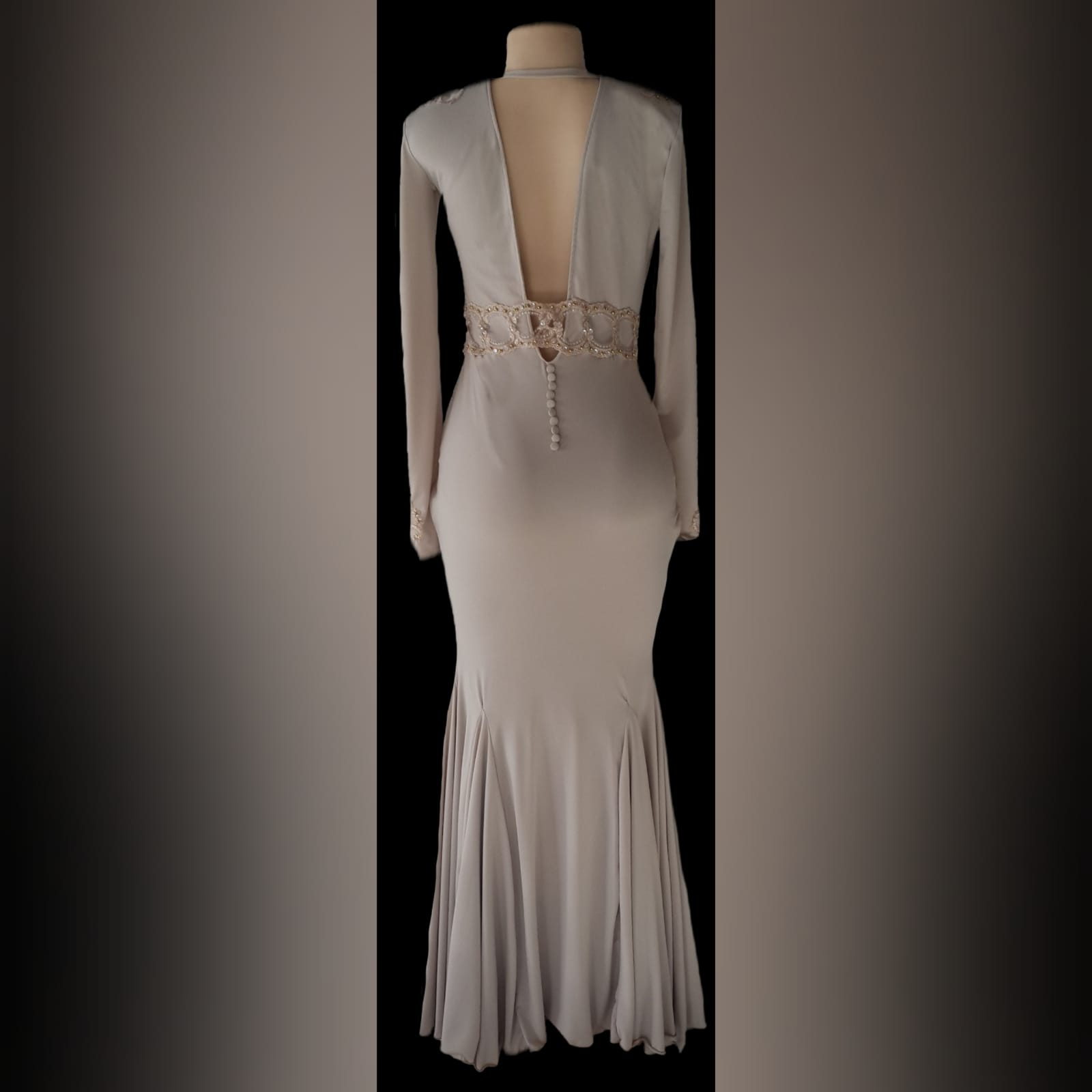 Plunging neckline beige prom dance dress 6 beige soft mermaid, prom dance dress with a plunging neckline and a v back. With long sleeves, detailed with gold applique, with gold beads, creating a belt. Applique on the shoulders and sleeve cuffs.