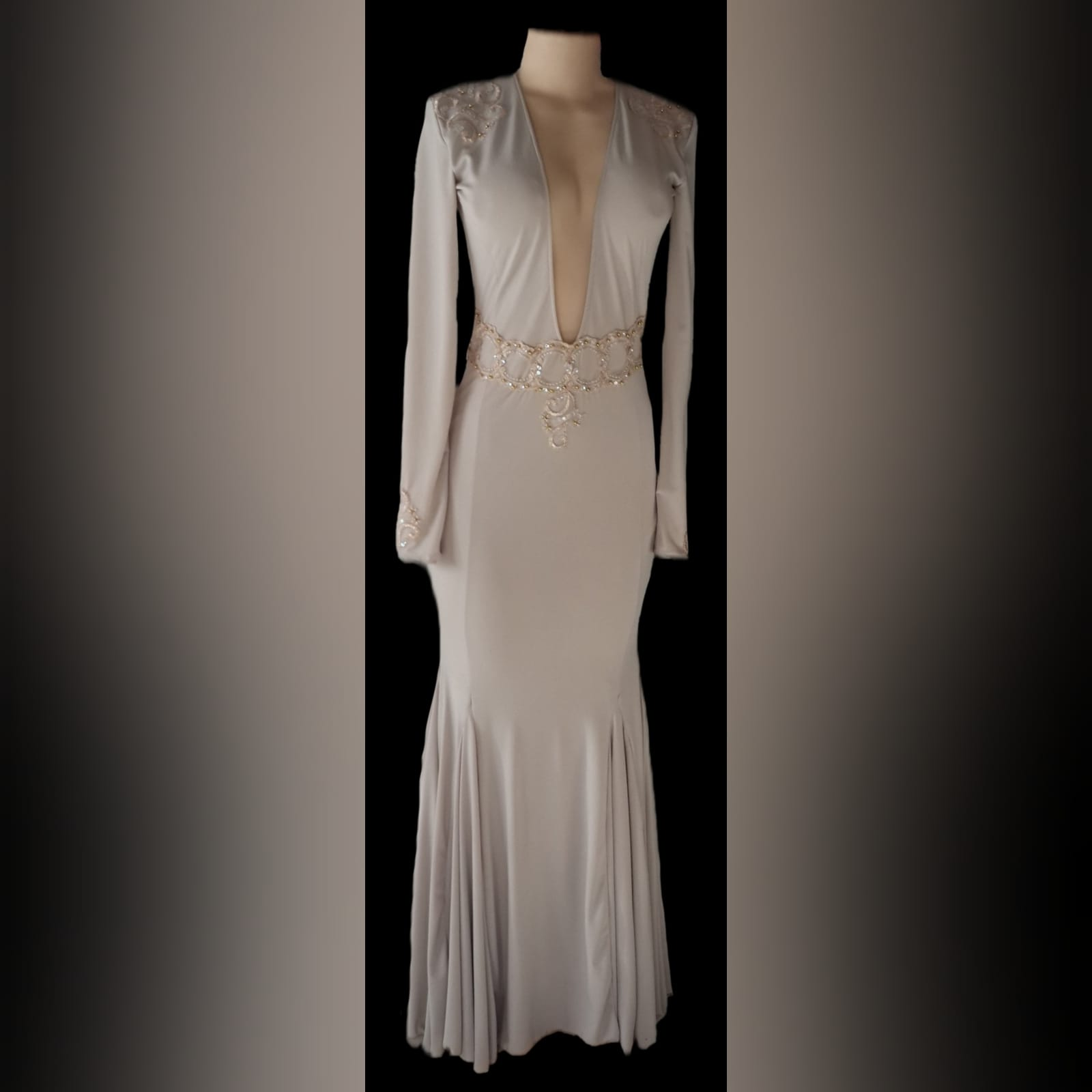 Plunging neckline beige prom dance dress 5 beige soft mermaid, prom dance dress with a plunging neckline and a v back. With long sleeves, detailed with gold applique, with gold beads, creating a belt. Applique on the shoulders and sleeve cuffs.