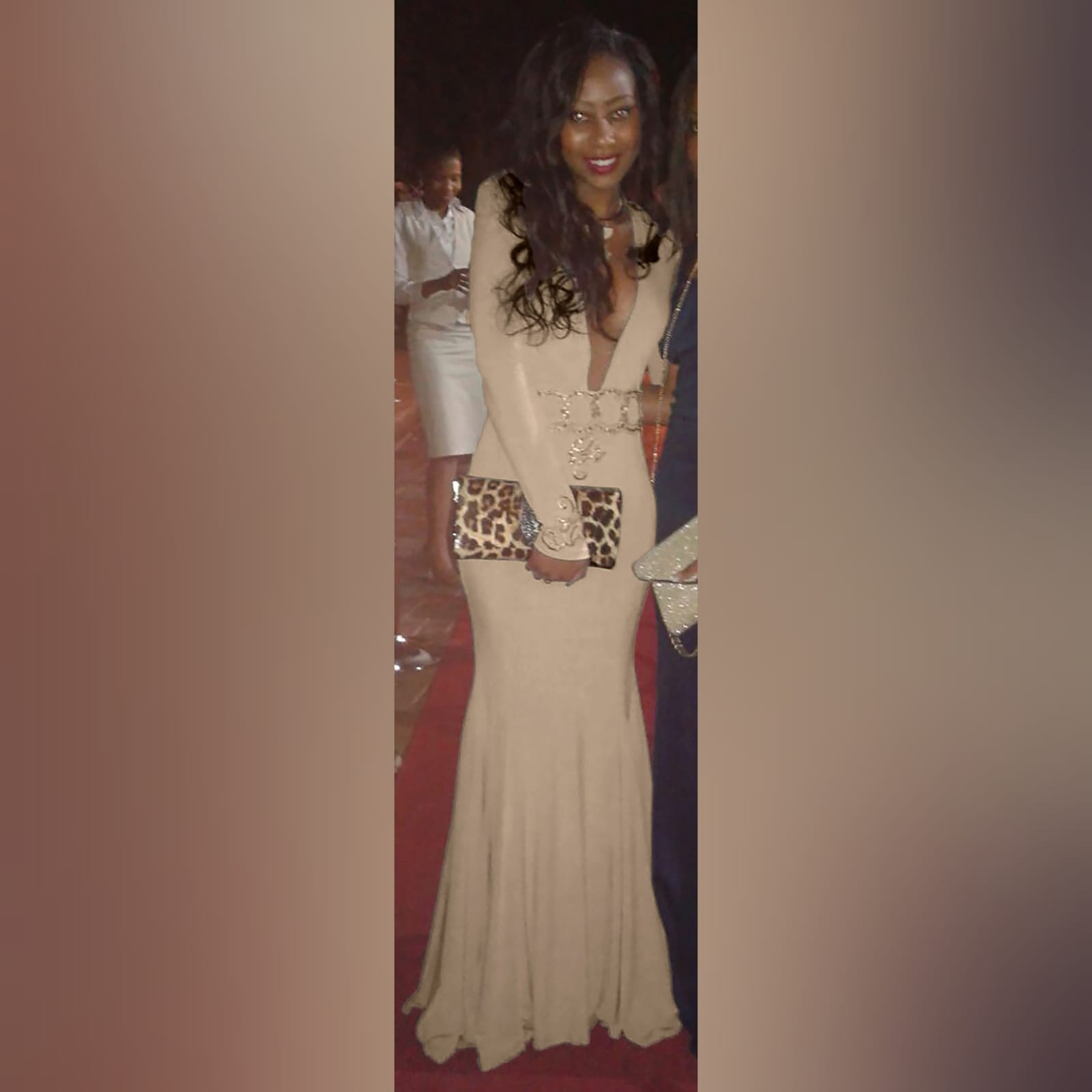 Plunging neckline beige prom dance dress 1 beige soft mermaid, prom dance dress with a plunging neckline and a v back. With long sleeves, detailed with gold applique, with gold beads, creating a belt. Applique on the shoulders and sleeve cuffs.