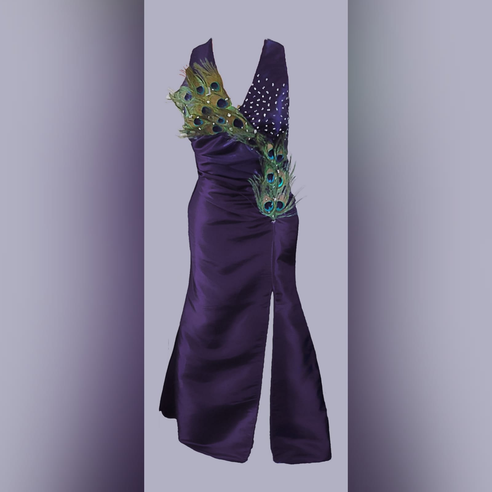 Purple peacock prom dance dress 2 purple prom dance dress detailed with peacock feathers and silver beads, with a slit, halter neck and matching hair accessory.
