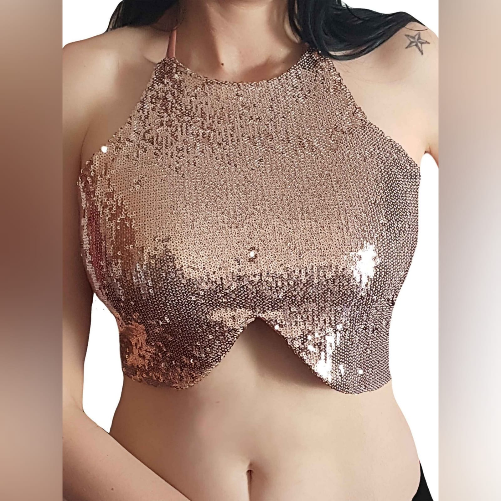 Rose gold sequins sexy top 2 a designer gold top that will make you sparkle when you out having fun. A short top with a high neck design and a rounded hemline. Naked back top with a tie-up design to adjust the way you like. A fun top that can be worn on several occasions. This shiny top is fun wear and great as a party top.