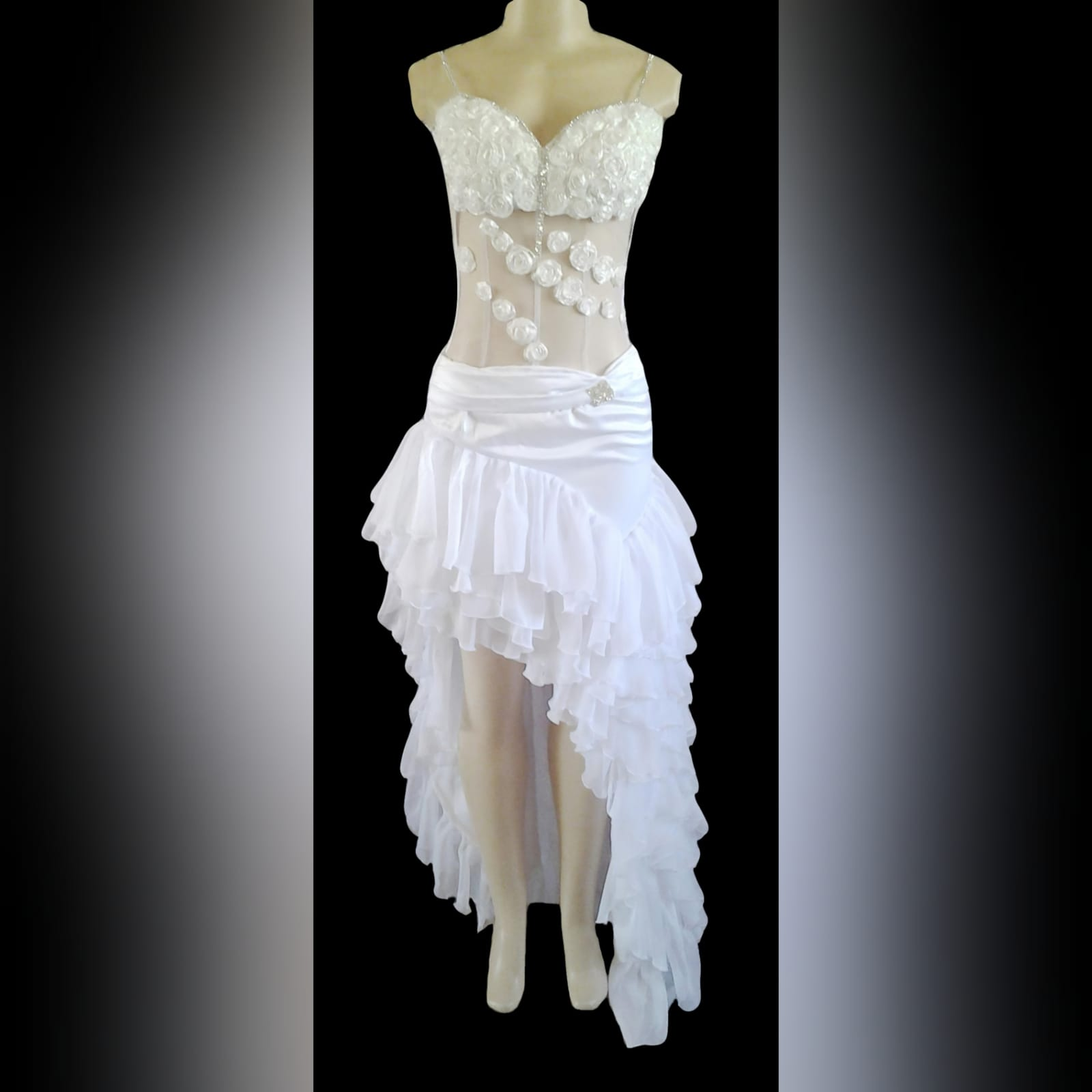 Sexy frilled white wedding dress 1 sexy white wedding dress with a sheer bodice. Bust covered with frilled flower detail going down the bodice with a pleated low waist belt and a hi-lo to the side of the wedding dress. This wedding dress is finished with chiffon frills and diamante detail. Each flower is detailed with clear beads.