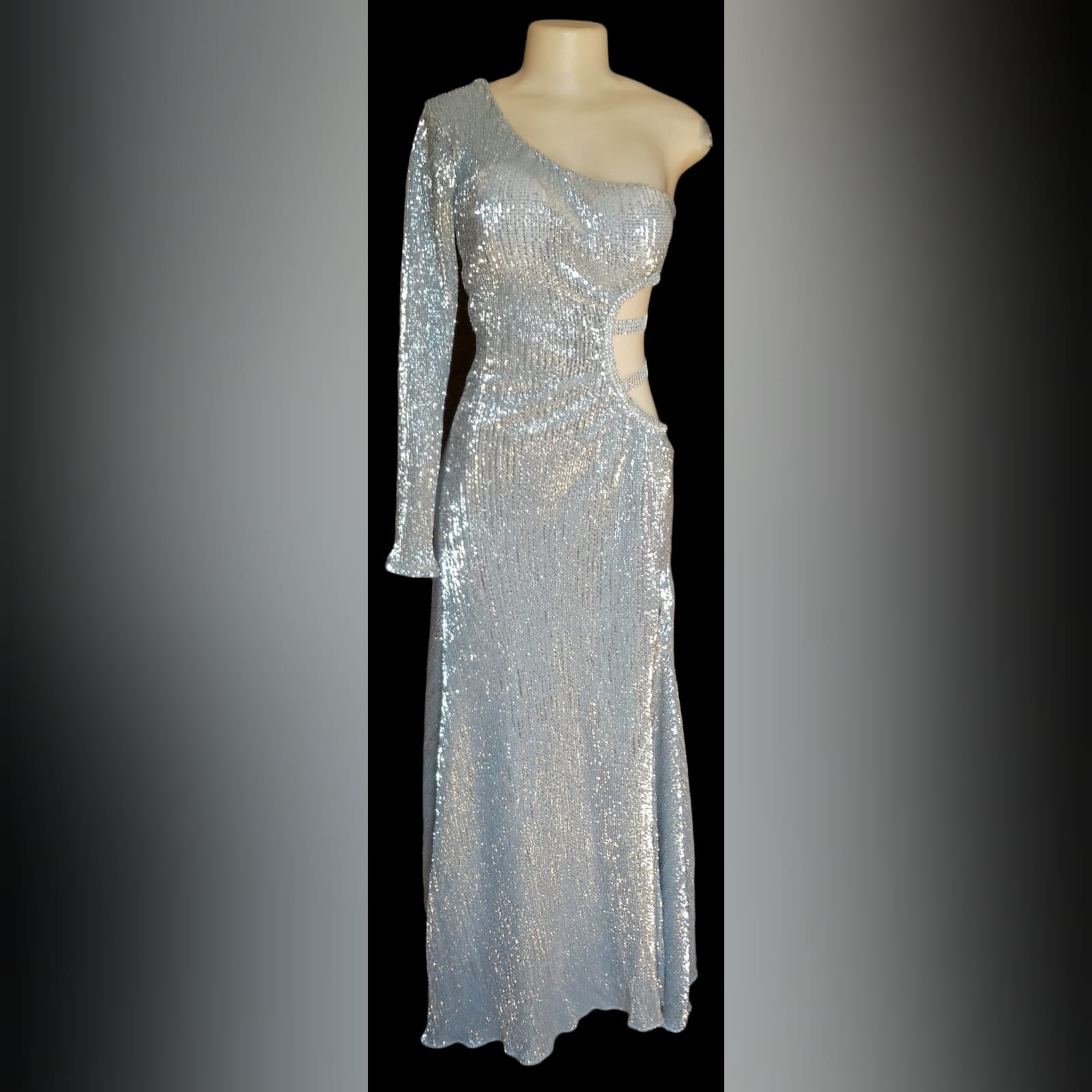 Silver sequins long sexy end year party dress 4 silver sequins long sexy end year party dress with side tummy and back opening detailed with straps, one sleeve and a train.