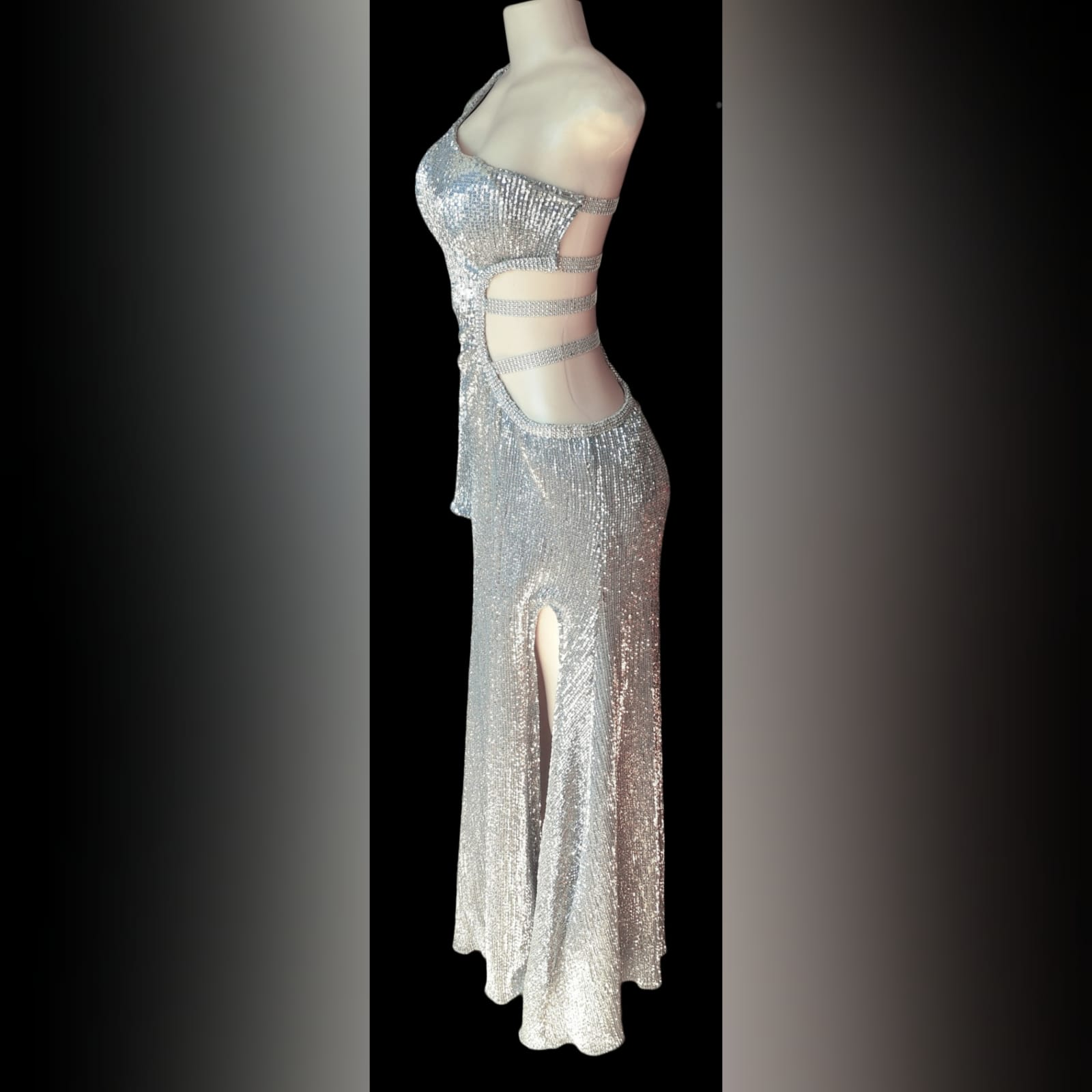 Silver sequins long sexy end year party dress 5 silver sequins long sexy end year party dress with side tummy and back opening detailed with straps, one sleeve and a train.