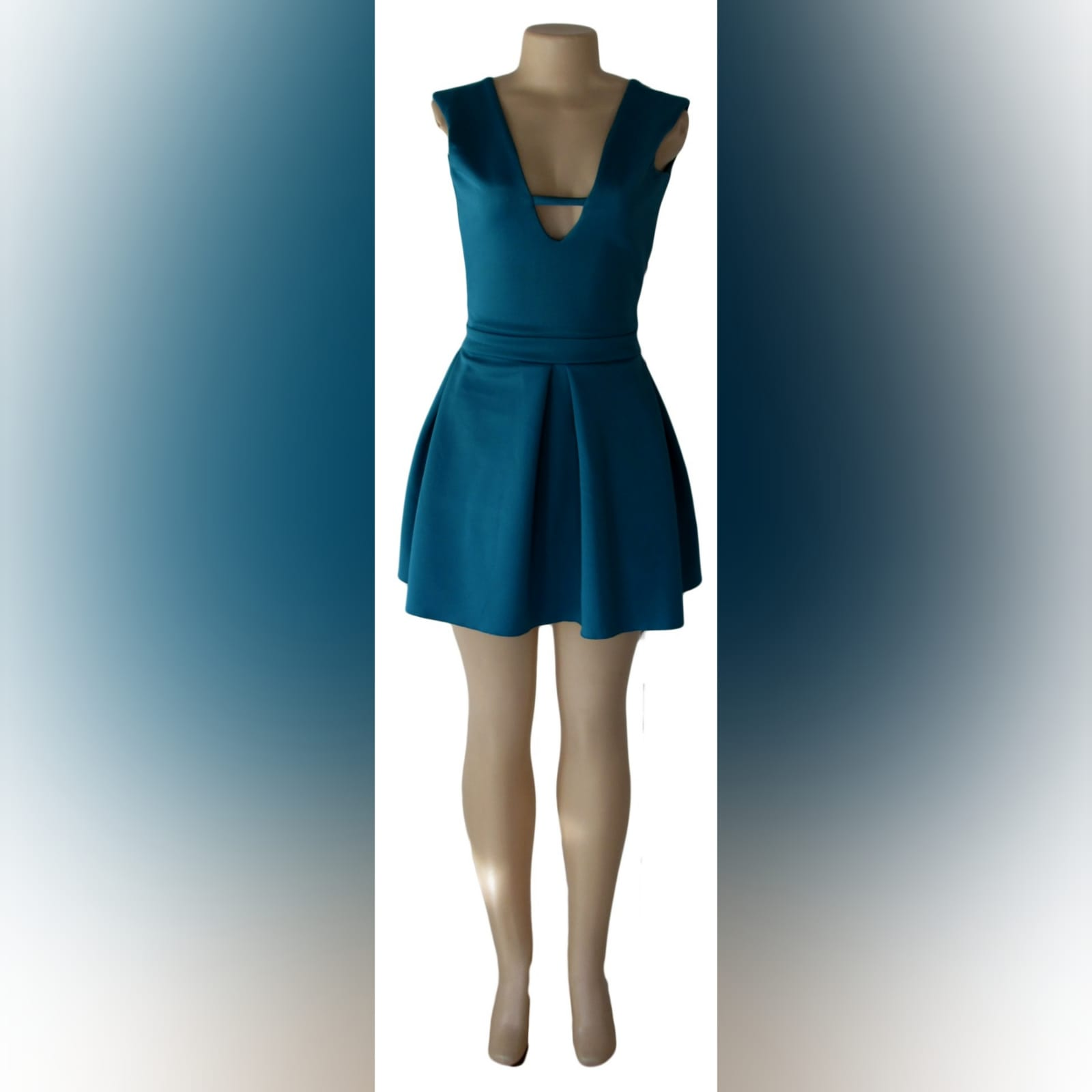 Turquoise green short smart casual dress 1 turquoise green short smart casual dress with a v neckline in front and a low v open back, with a waistband, and wide pleats on the bottom.