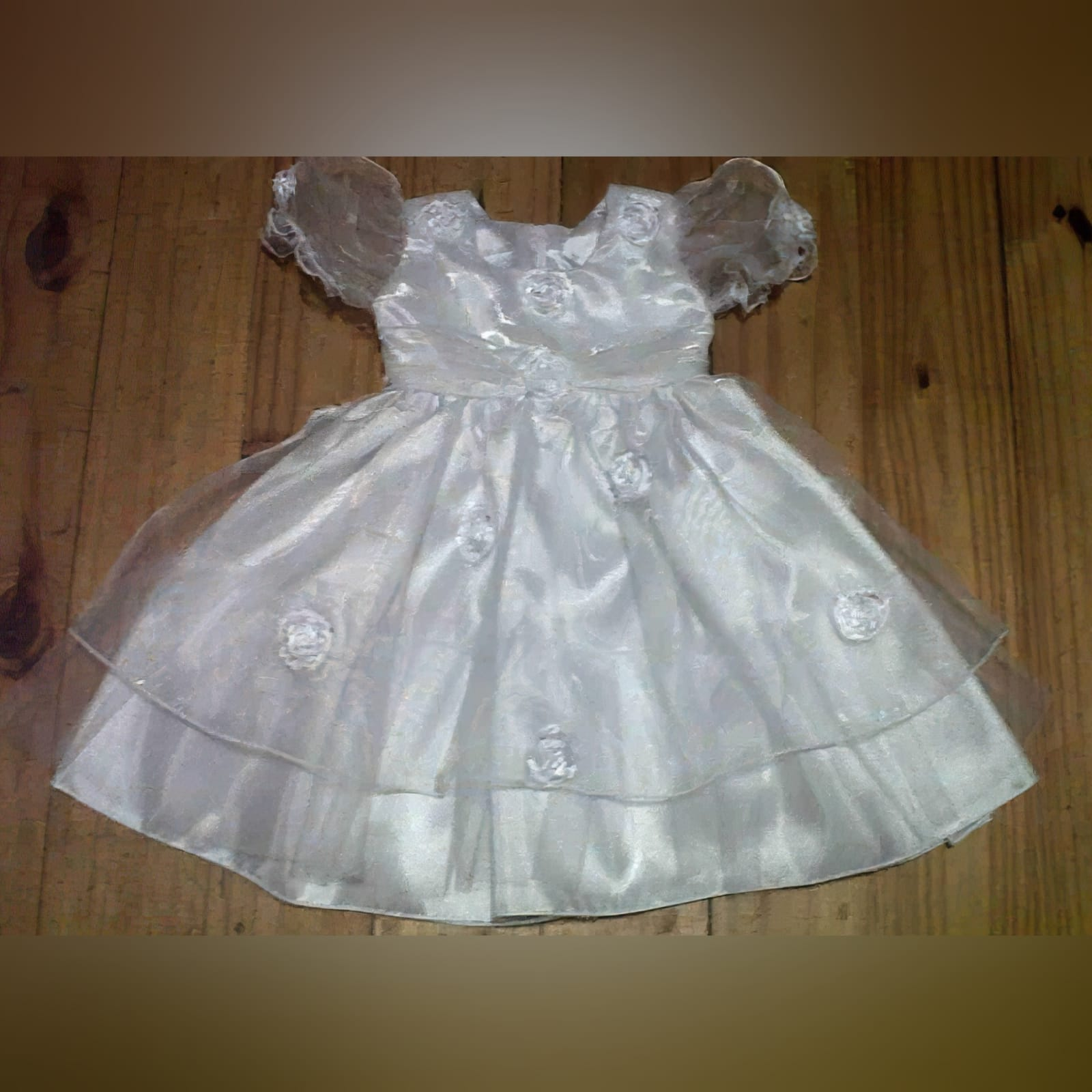 White baptism dress in crushed organza 2 white baptism dress made in satin with a double layer of crushed organza, beaded flowers on the bodice with ribbon and short bubble sleeves.