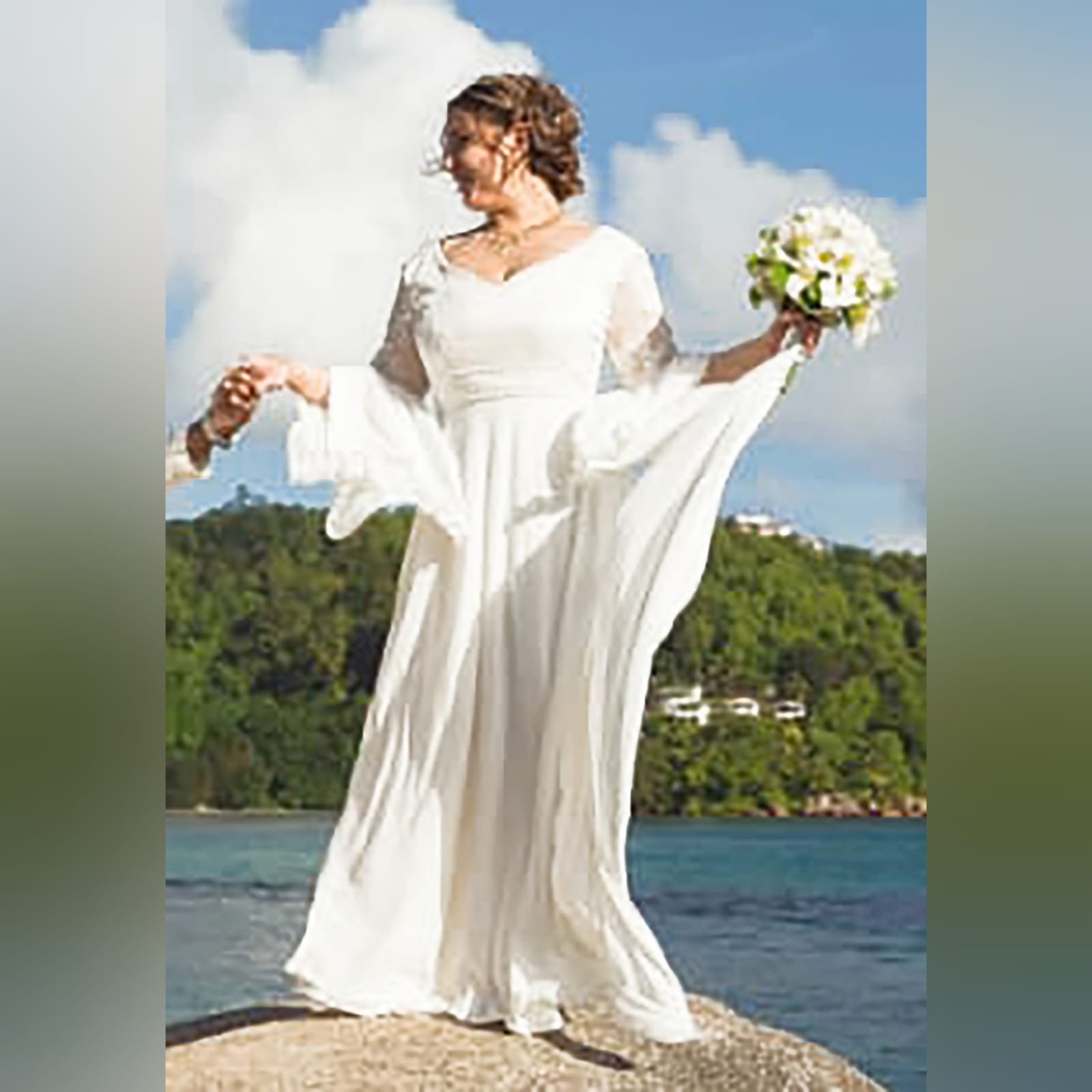 White flowy lace bodice wedding dress 1 white flowy lace bodice wedding dress. With bell sleeve and train. Sleeve and belt detailed with pearls. Stunnning wedding dress awesome for a beach wedding.