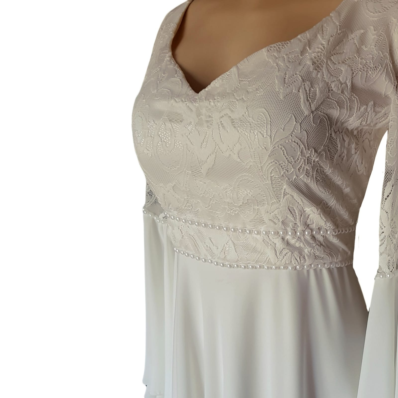White flowy lace bodice wedding dress 8 white flowy lace bodice wedding dress. With bell sleeve and train. Sleeve and belt detailed with pearls. Stunnning wedding dress awesome for a beach wedding.