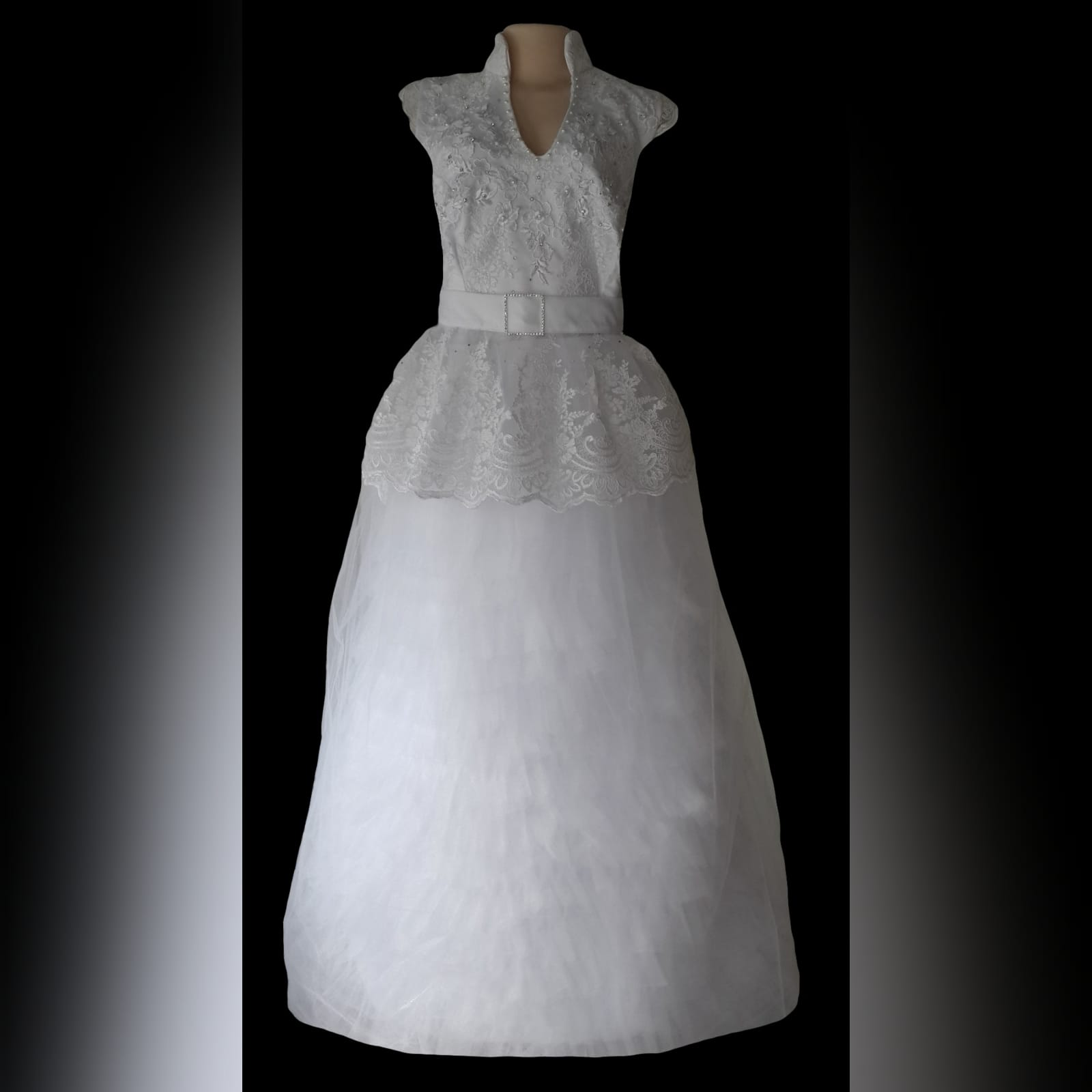 White 3 piece lace wedding dress with v neckline 2 white 3 piece lace wedding dress, detailed with pearls and beads. White mini wedding dress with peplum and pop up collar. With a removable tulle skirt.