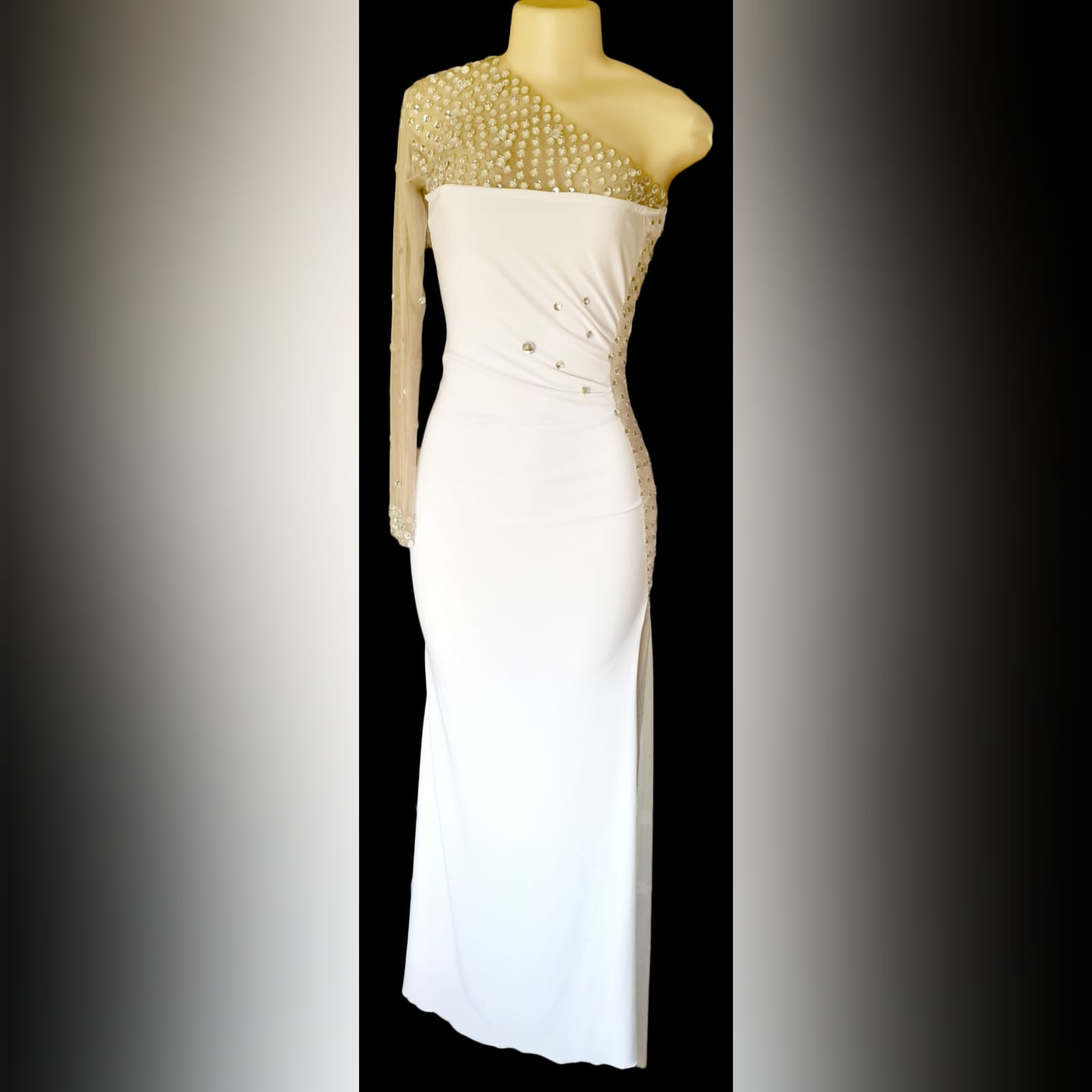 White and silver long fitted new years party dress 5 white and silver long fitted new years party dress. With an angled neckline and one sleeve detailed with silver beads. With a sheer side panel with beads creating a slit.