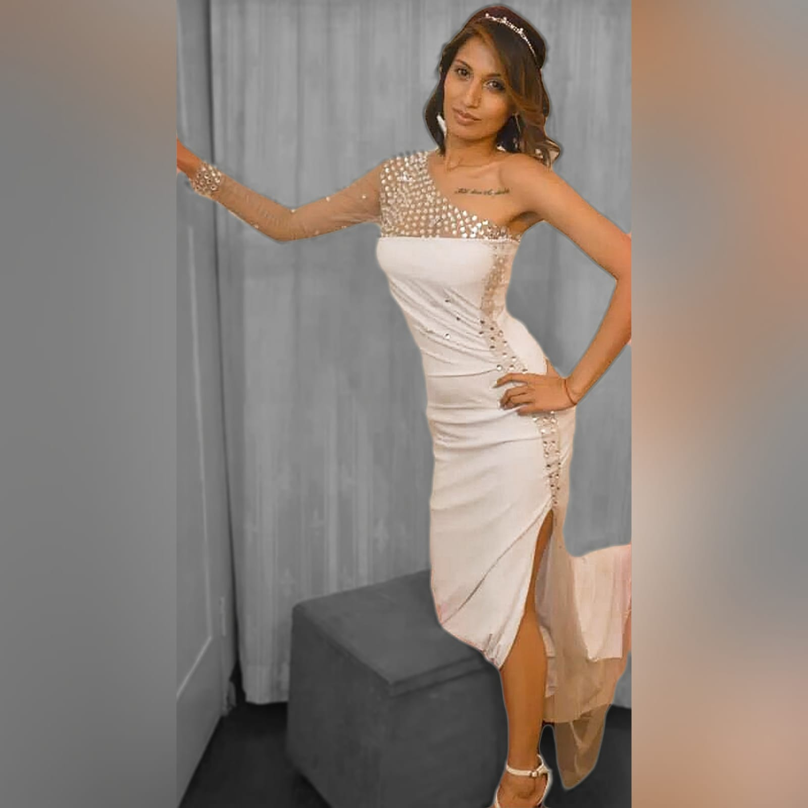 White and silver long fitted new years party dress 1 white and silver long fitted new years party dress. With an angled neckline and one sleeve detailed with silver beads. With a sheer side panel with beads creating a slit.