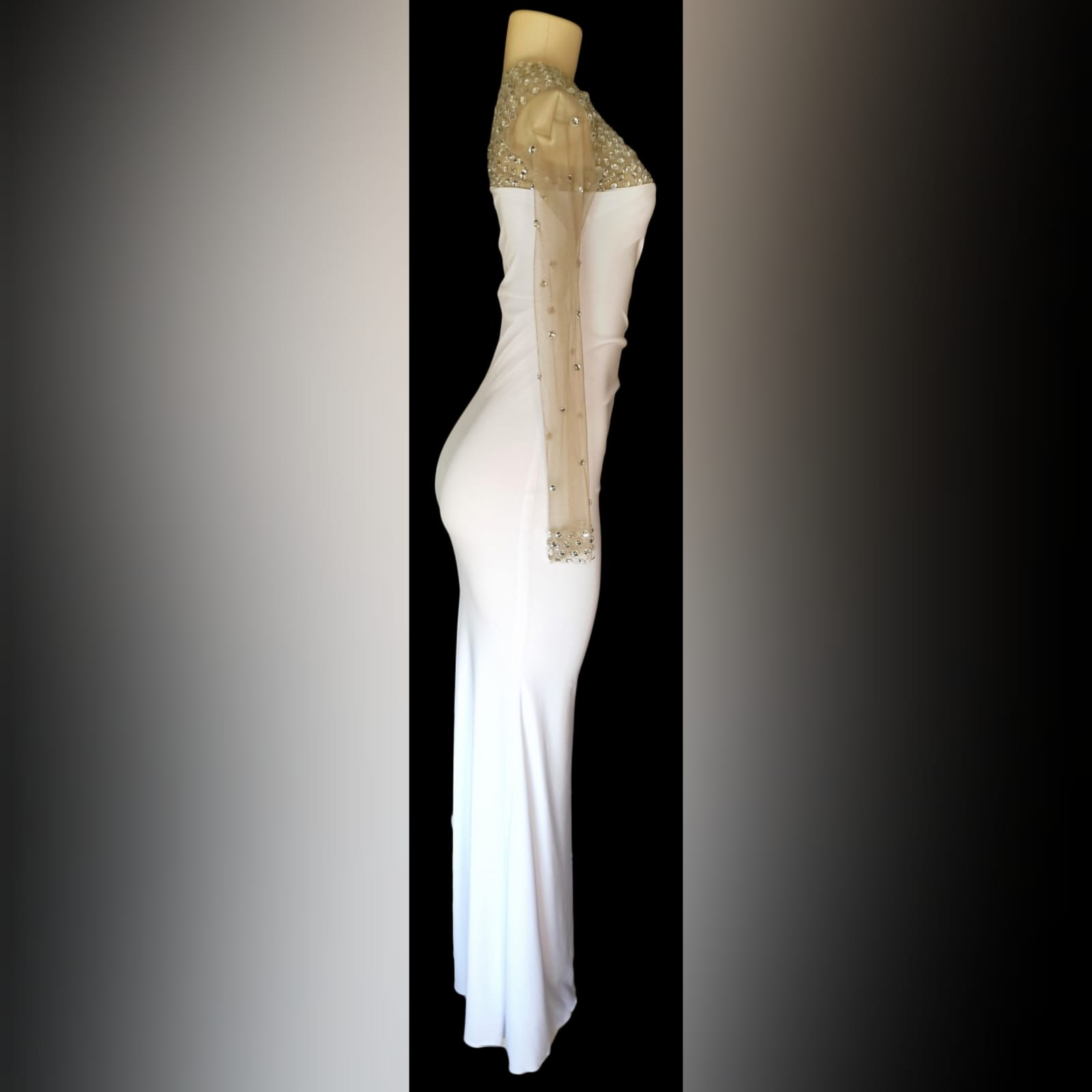 White and silver long fitted new years party dress 6 white and silver long fitted new years party dress. With an angled neckline and one sleeve detailed with silver beads. With a sheer side panel with beads creating a slit.