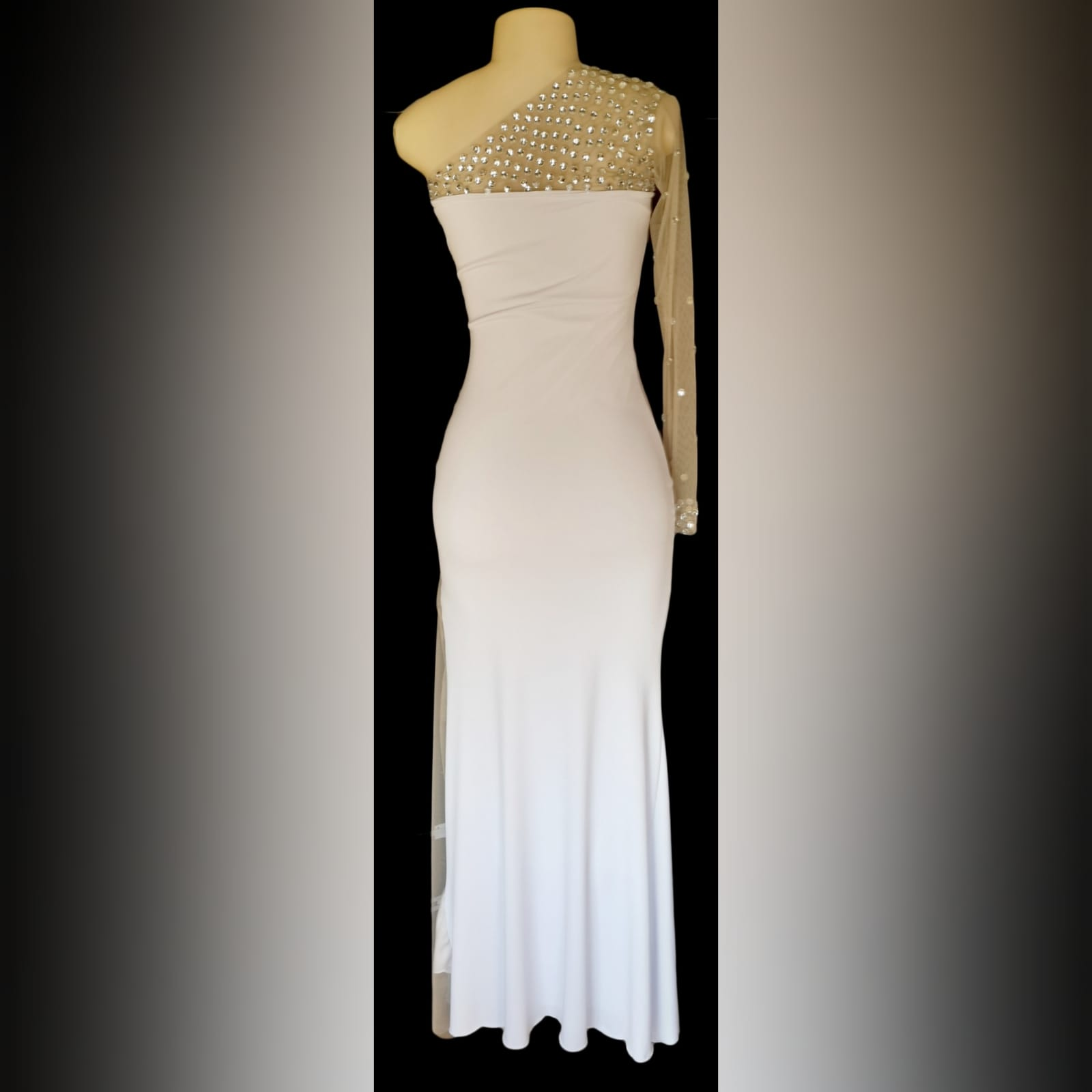 White and silver long fitted new years party dress 7 white and silver long fitted new years party dress. With an angled neckline and one sleeve detailed with silver beads. With a sheer side panel with beads creating a slit.