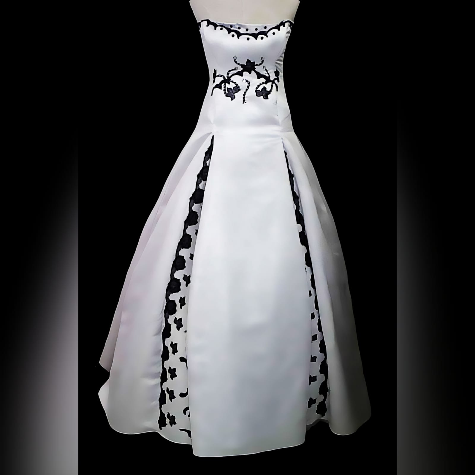 White & black panelled boob tube ballgown wedding dress 1 white panelled boob tube ballgown wedding dress with black lace detail spread throughout the hidden panels of wedding dress and on the under bust area. A lace up back in with black ribbon. When you walk with this dress, it opens to reveal the black lace.