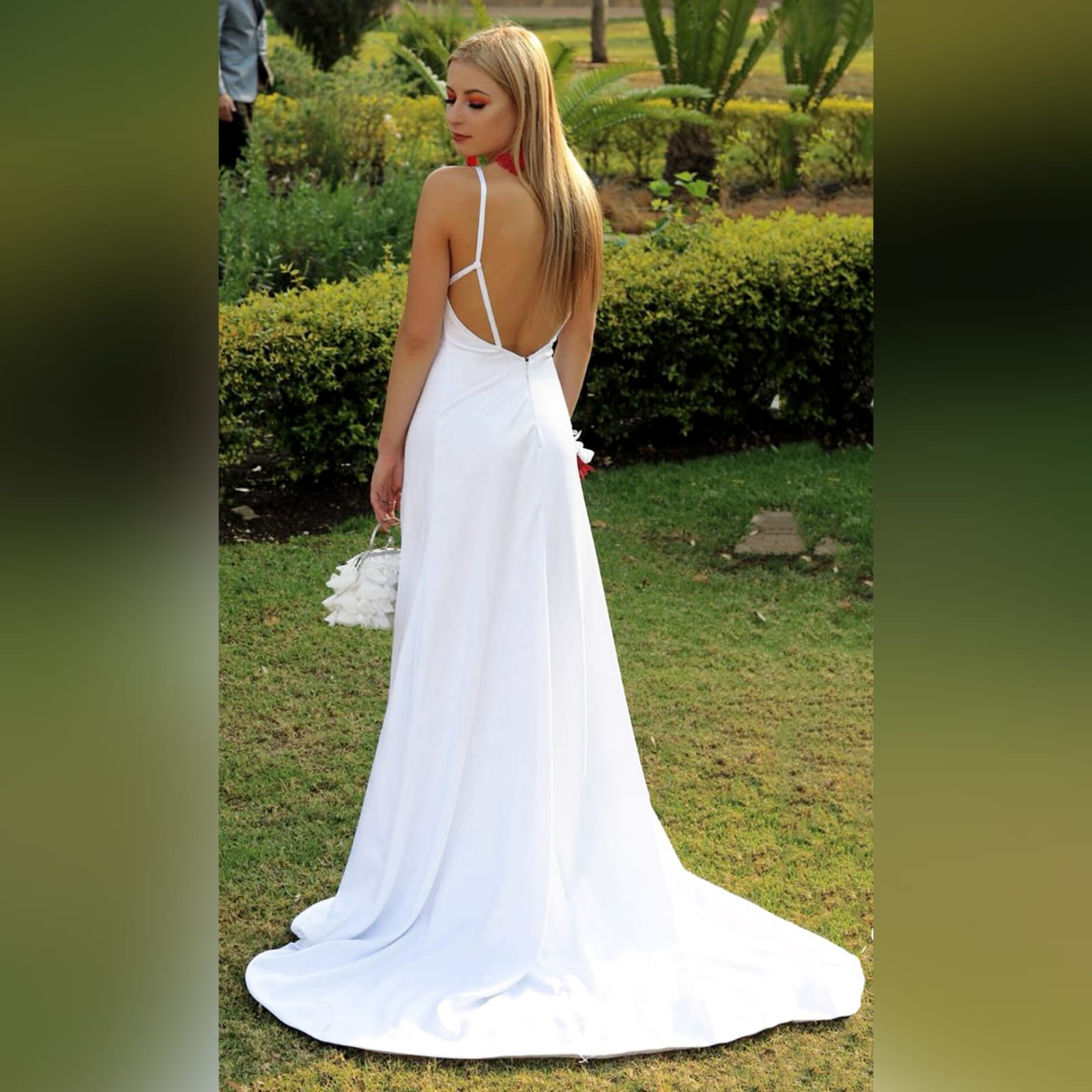White satin long prom dress with a low open back 1 white satin long prom dress with a low open back, with strap detail. Straight neckline, 2 slits and a train.