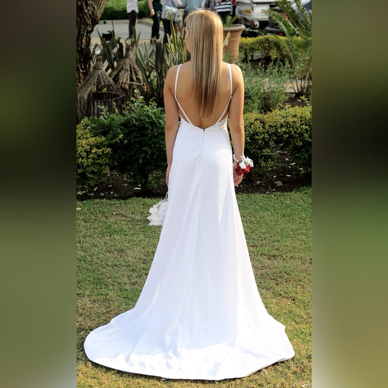 White satin long prom dress with a low open back 4 white satin long prom dress with a low open back, with strap detail. Straight neckline, 2 slits and a train.
