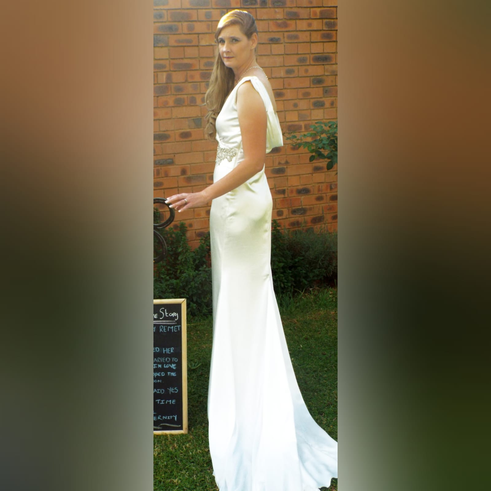 White satin soft mermaid wedding dress with silver belt detail 1 white satin soft mermaid wedding dress, cross busted neckline, open cowl neck back. Angled belt with diamante detail. Train with train hookup.