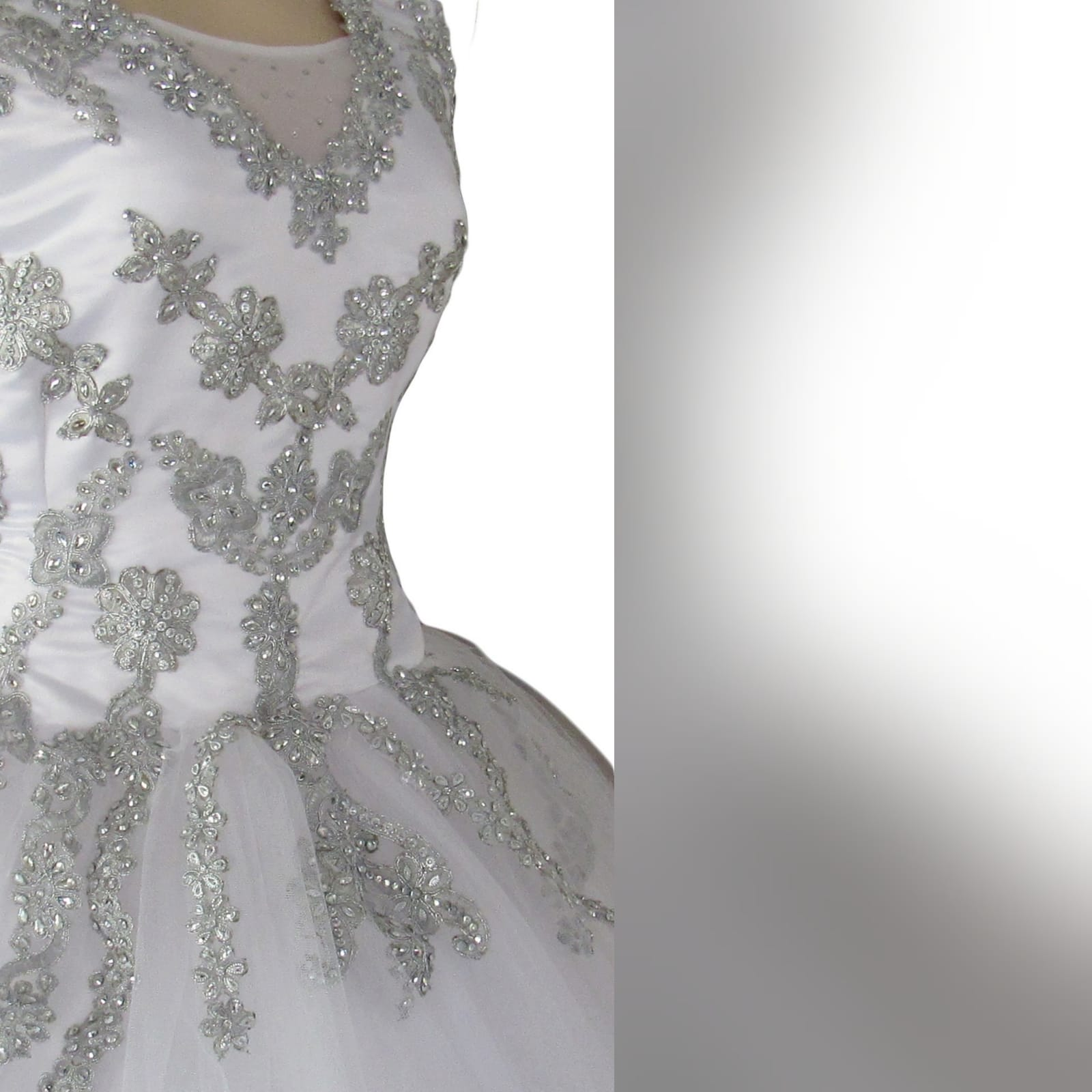 White & silver ball gown wedding dress 11 white & silver ballgown wedding dress. Bodice detailed with silver detail and beads. Falling to the ballgown. Back detailed with silver covered buttons.