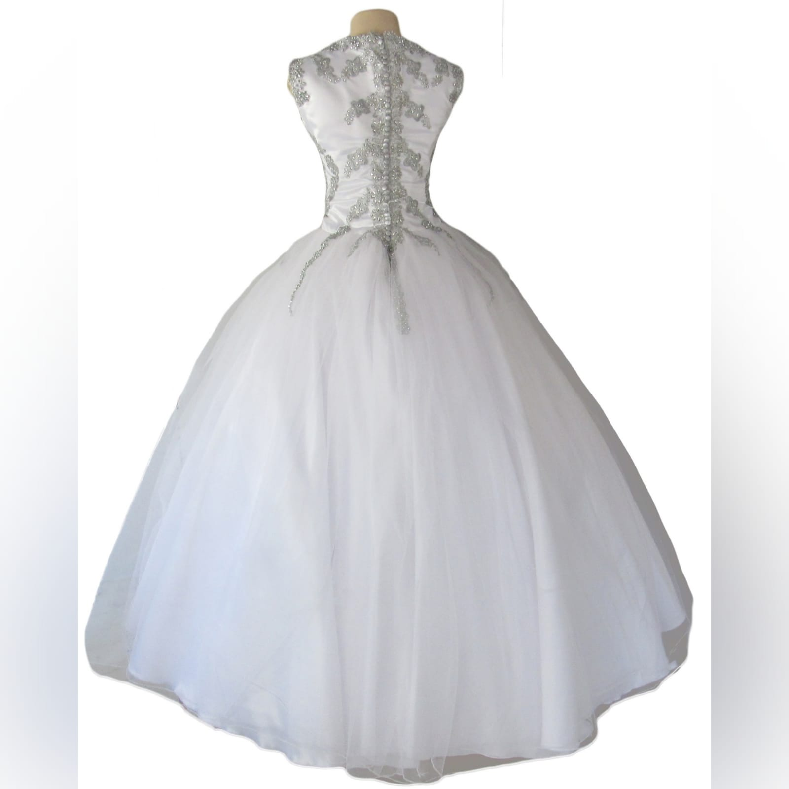 White & silver ball gown wedding dress 10 white & silver ballgown wedding dress. Bodice detailed with silver detail and beads. Falling to the ballgown. Back detailed with silver covered buttons.