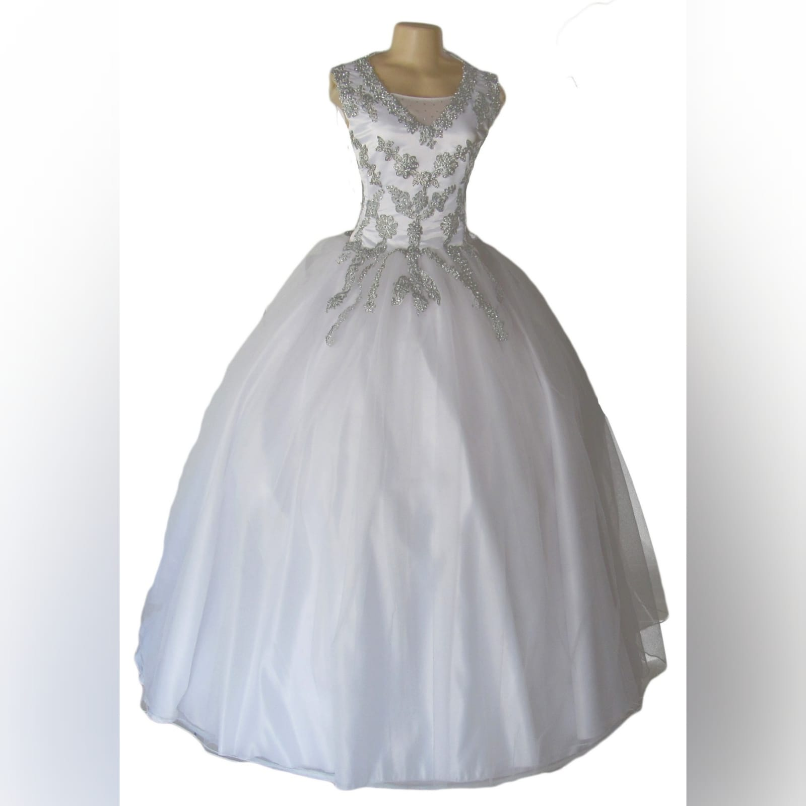 White & silver ball gown wedding dress 7 white & silver ballgown wedding dress. Bodice detailed with silver detail and beads. Falling to the ballgown. Back detailed with silver covered buttons.