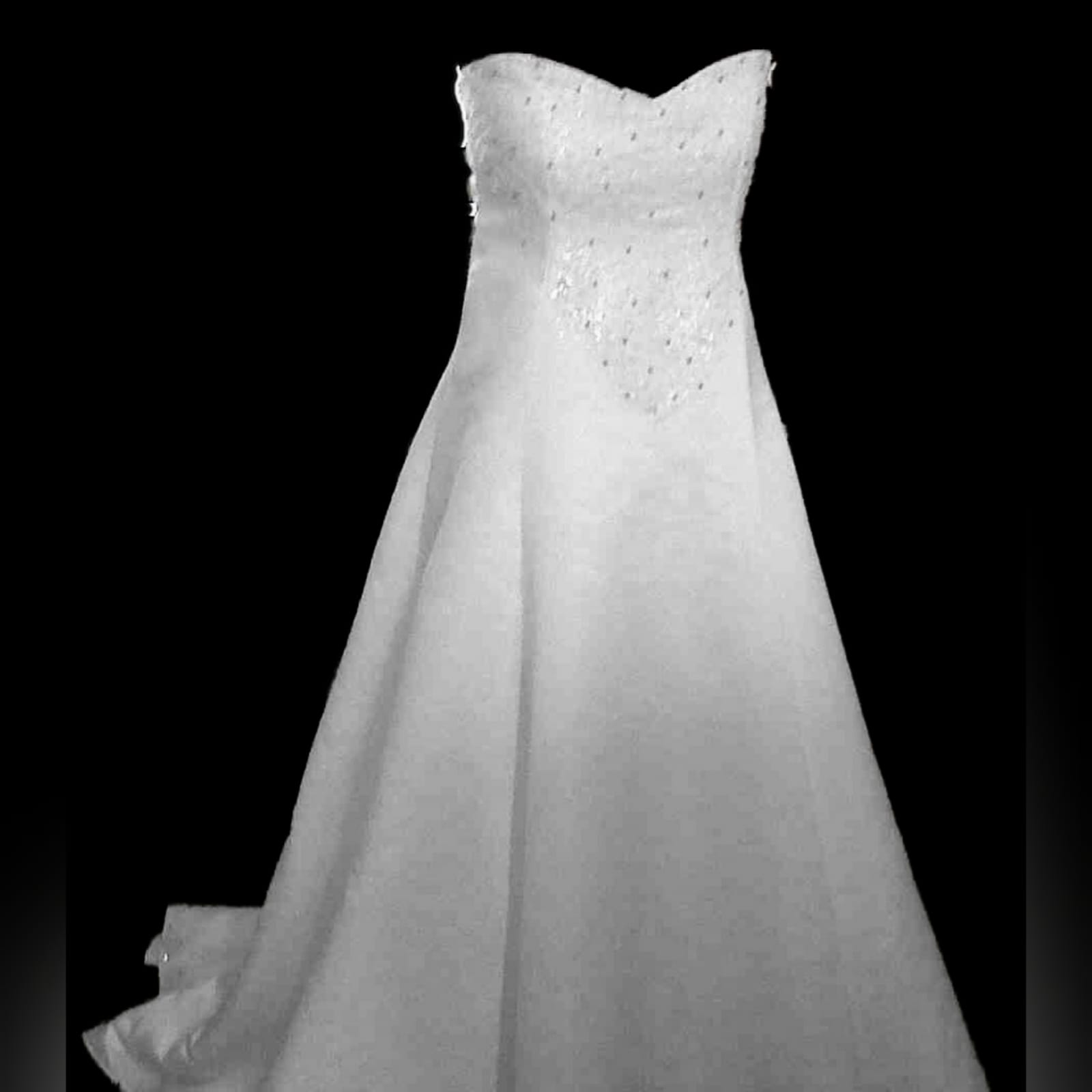 White & glitter ball gown wedding dress 4 white & glitter ball gown wedding dress. Bodice detailed with silver detail and beads. Falling to the ballgown. Back detailed with silver covered buttons.