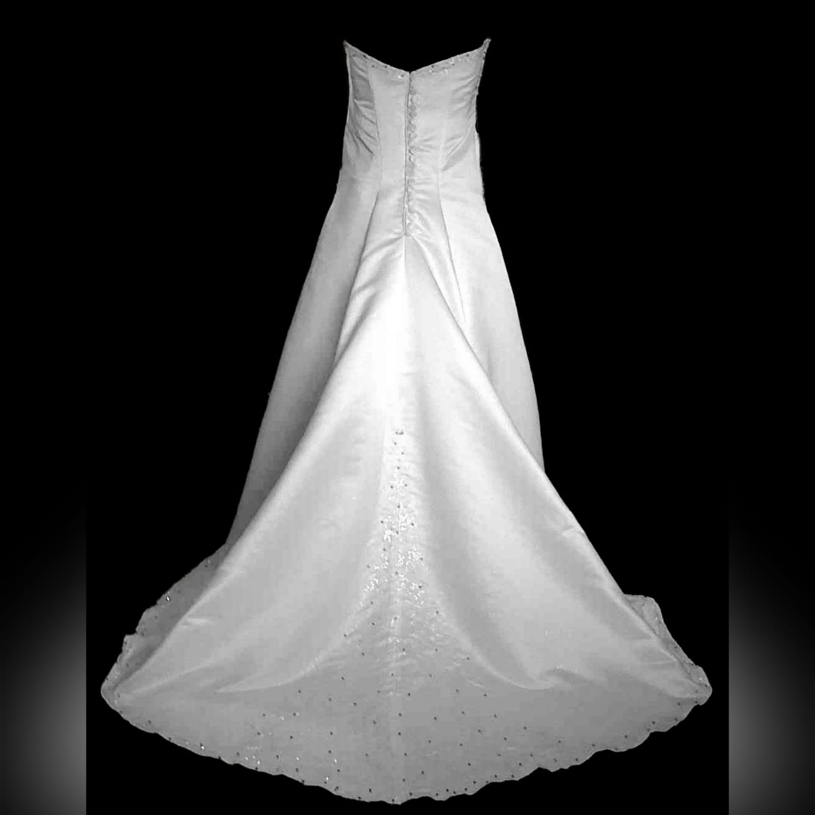 White & glitter ball gown wedding dress 5 white & glitter ball gown wedding dress. Bodice detailed with silver detail and beads. Falling to the ballgown. Back detailed with silver covered buttons.
