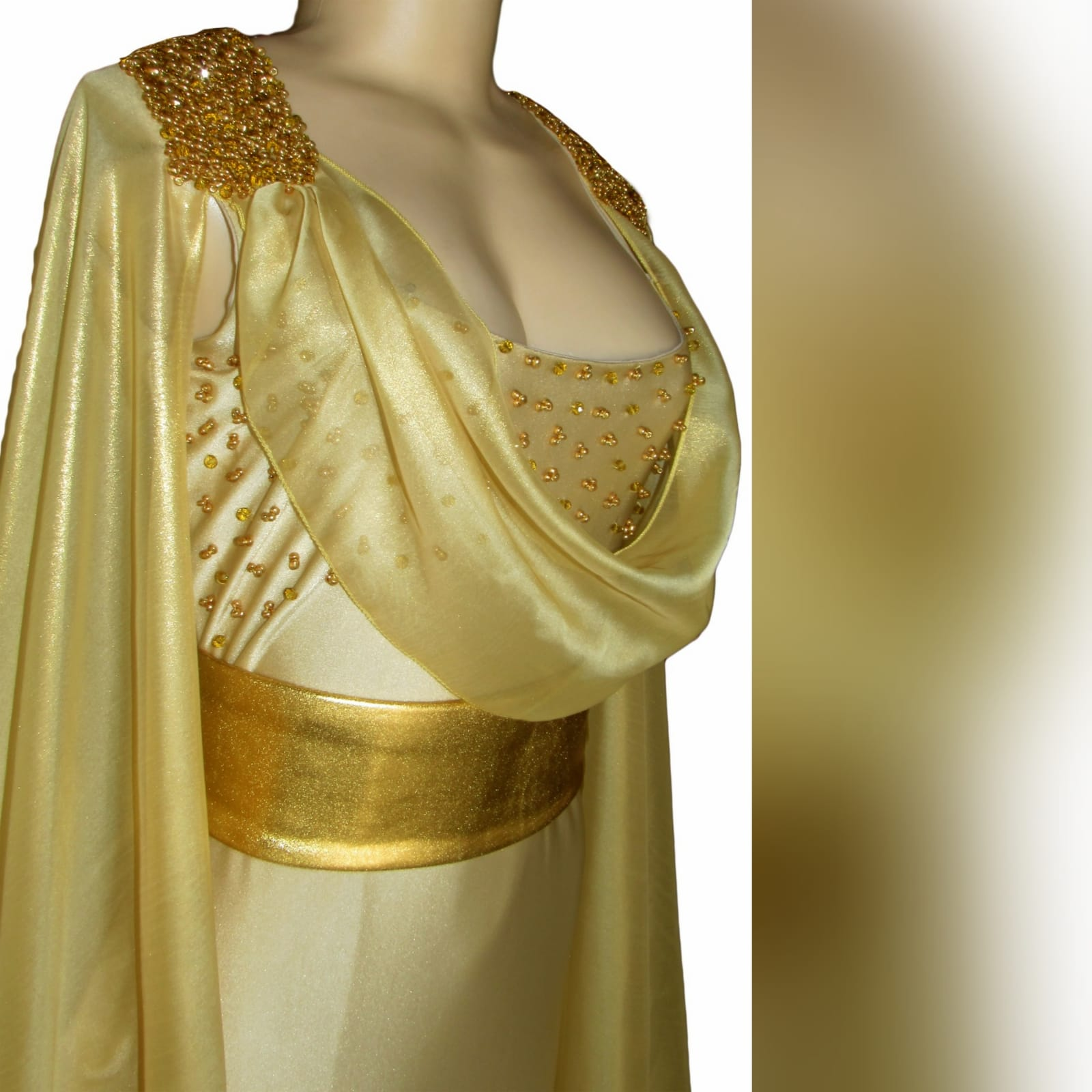 Gold long goddess inspired prom dress 5 gold long goddess inspired prom dress. Long fitted dress with a high slit and a train. With bust detailed with gold beads and a chiffon cowl neck, with a dramatic chiffon cape beaded on the shoulders. With a long train.