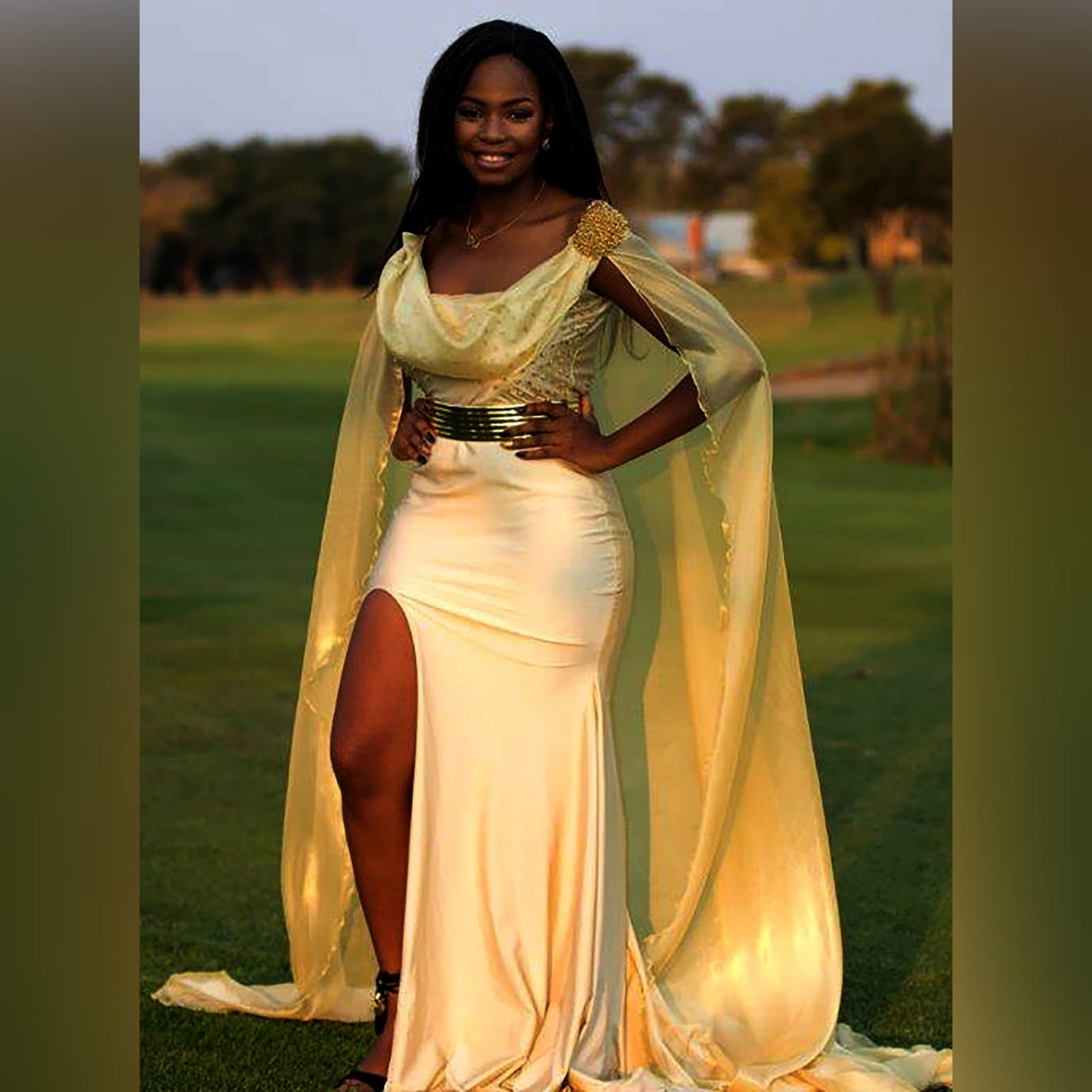 Gold long goddess inspired prom dress 1 gold long goddess inspired prom dress. Long fitted dress with a high slit and a train. With bust detailed with gold beads and a chiffon cowl neck, with a dramatic chiffon cape beaded on the shoulders. With a long train.