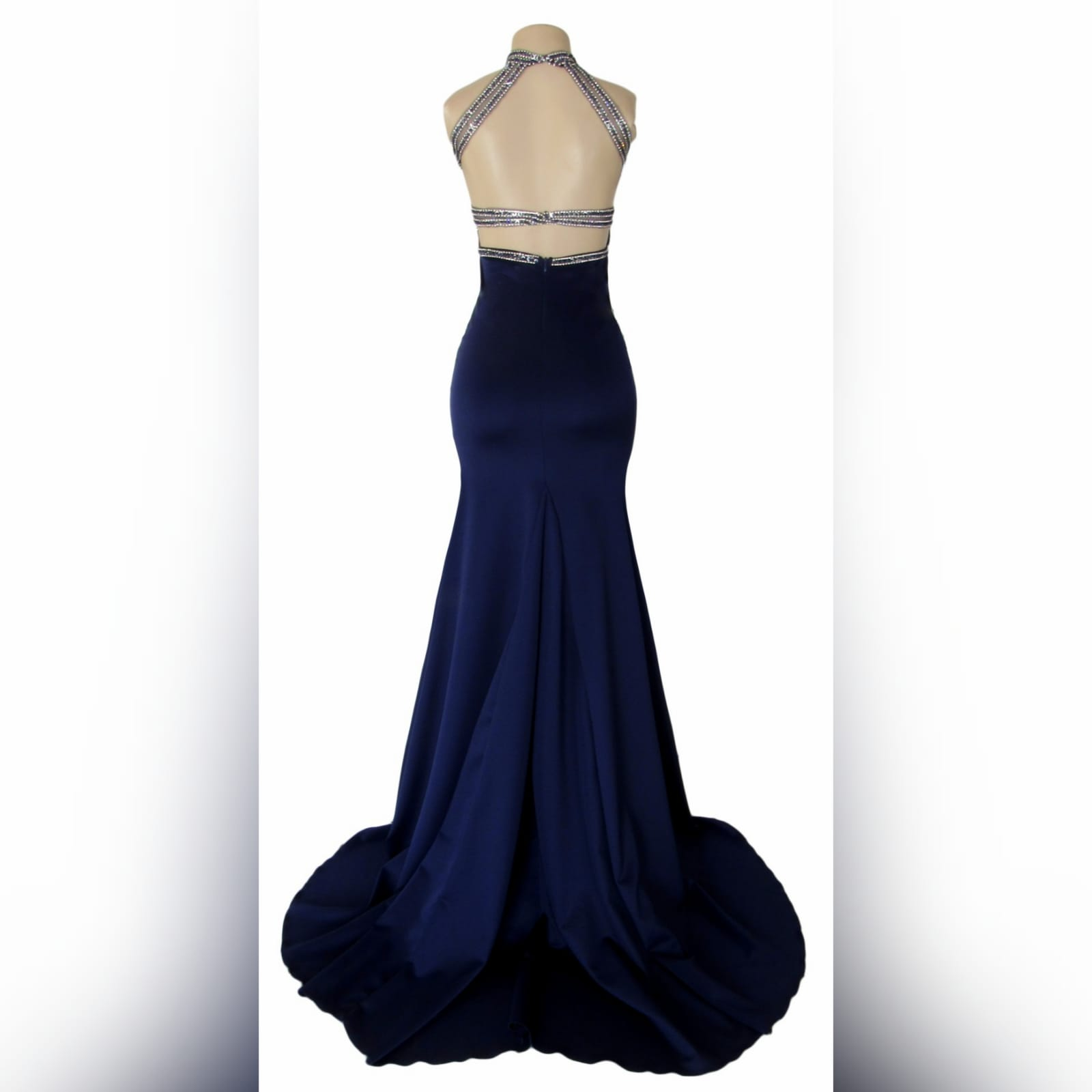 Navy blue silver beaded prom dress 2 navy blue silver beaded prom dress with an illusion neckline and a choker effect. Backless design detailed with beaded straps. Fitted bottom with a slit and a train.