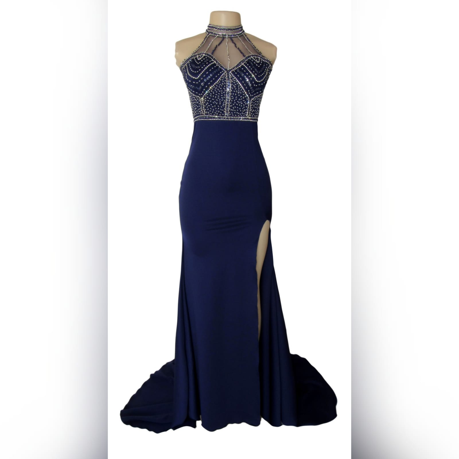 Navy blue silver beaded prom dress 4 navy blue silver beaded prom dress with an illusion neckline and a choker effect. Backless design detailed with beaded straps. Fitted bottom with a slit and a train.