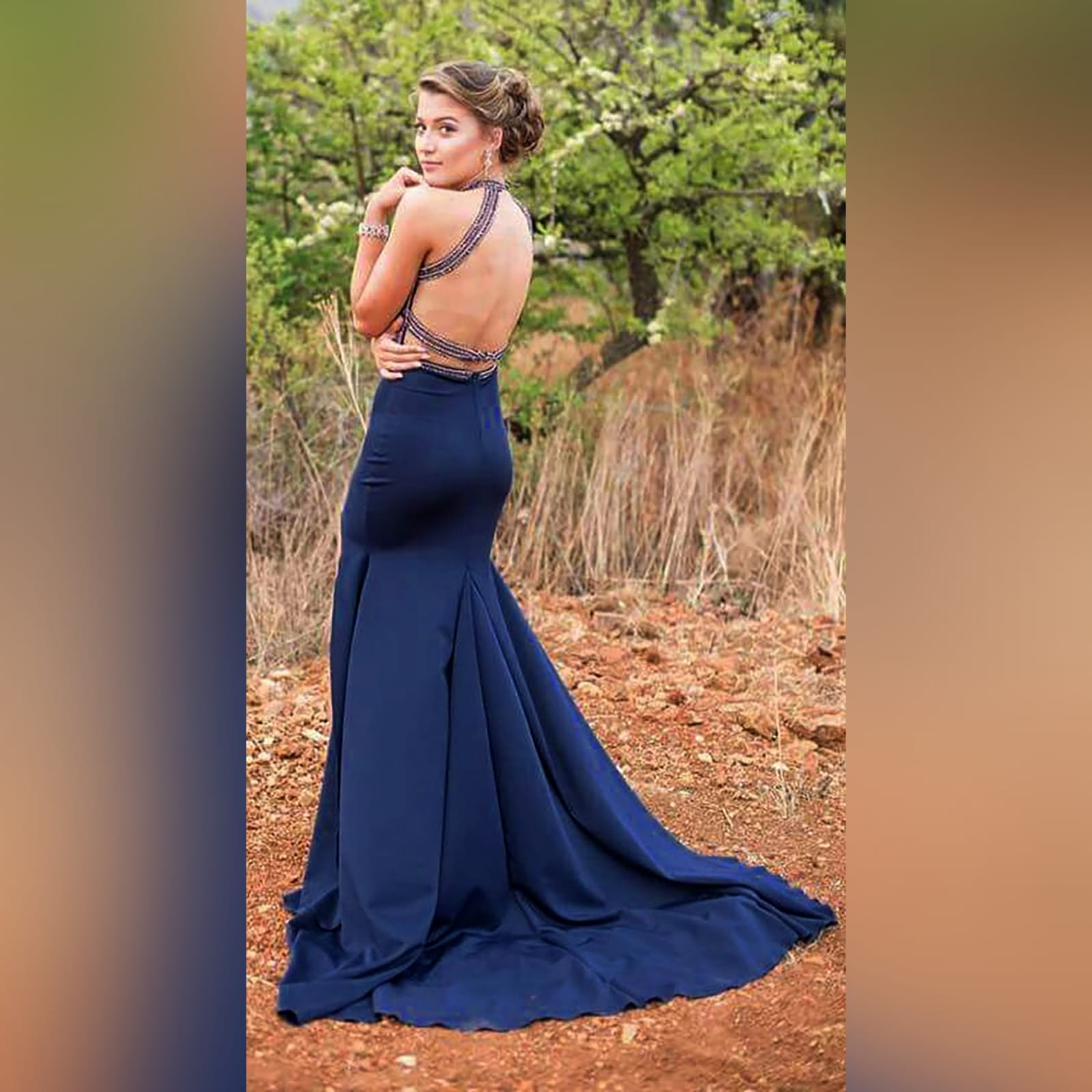 Navy blue silver beaded prom dress 6 navy blue silver beaded prom dress with an illusion neckline and a choker effect. Backless design detailed with beaded straps. Fitted bottom with a slit and a train.