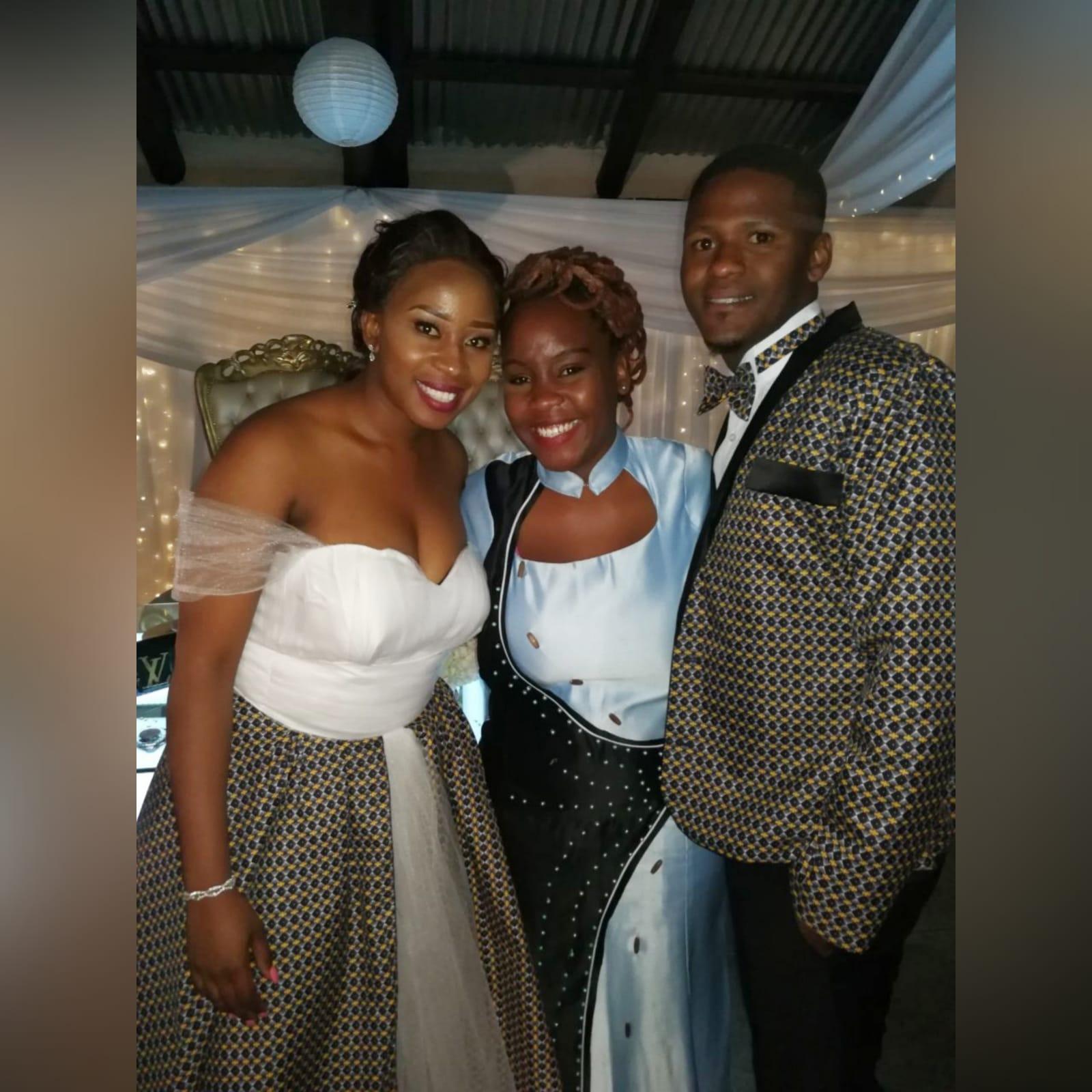 Vestido de noiva tradicional africano branco e castanho 3 vestido de noiva tradicional africano branco e castanho. Decote coração, alças fora de ombro em tule, com uma saia em tule e uma sobreposição de tecido tradicional africano. Casaco do noivo combinando e gravata-borboleta