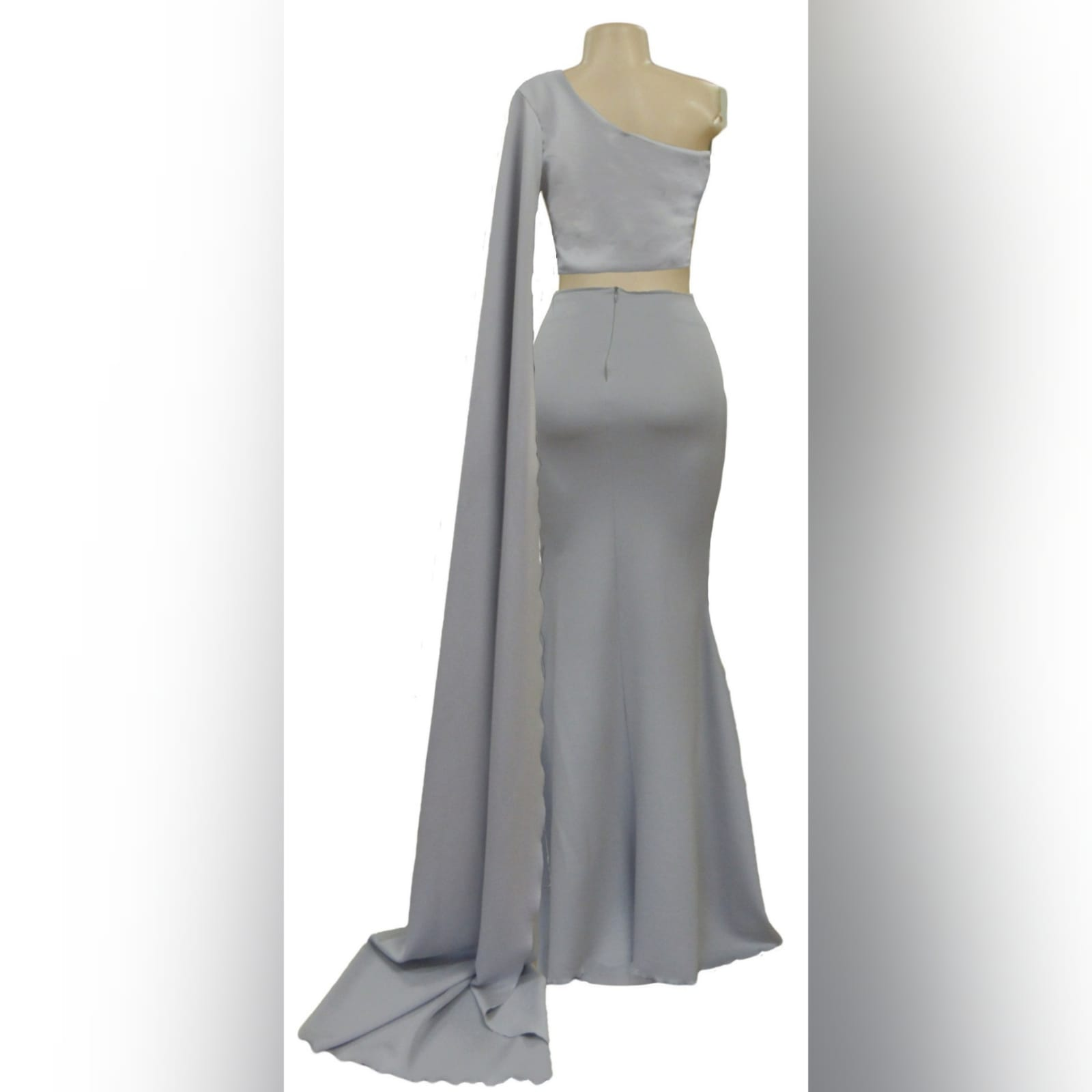 2 piece light grey prom dress 5 2 piece light grey prom dress, crop top with a single shoulder and a long wide sleeve creating a train. With a fitted long skirt, with a high slit.