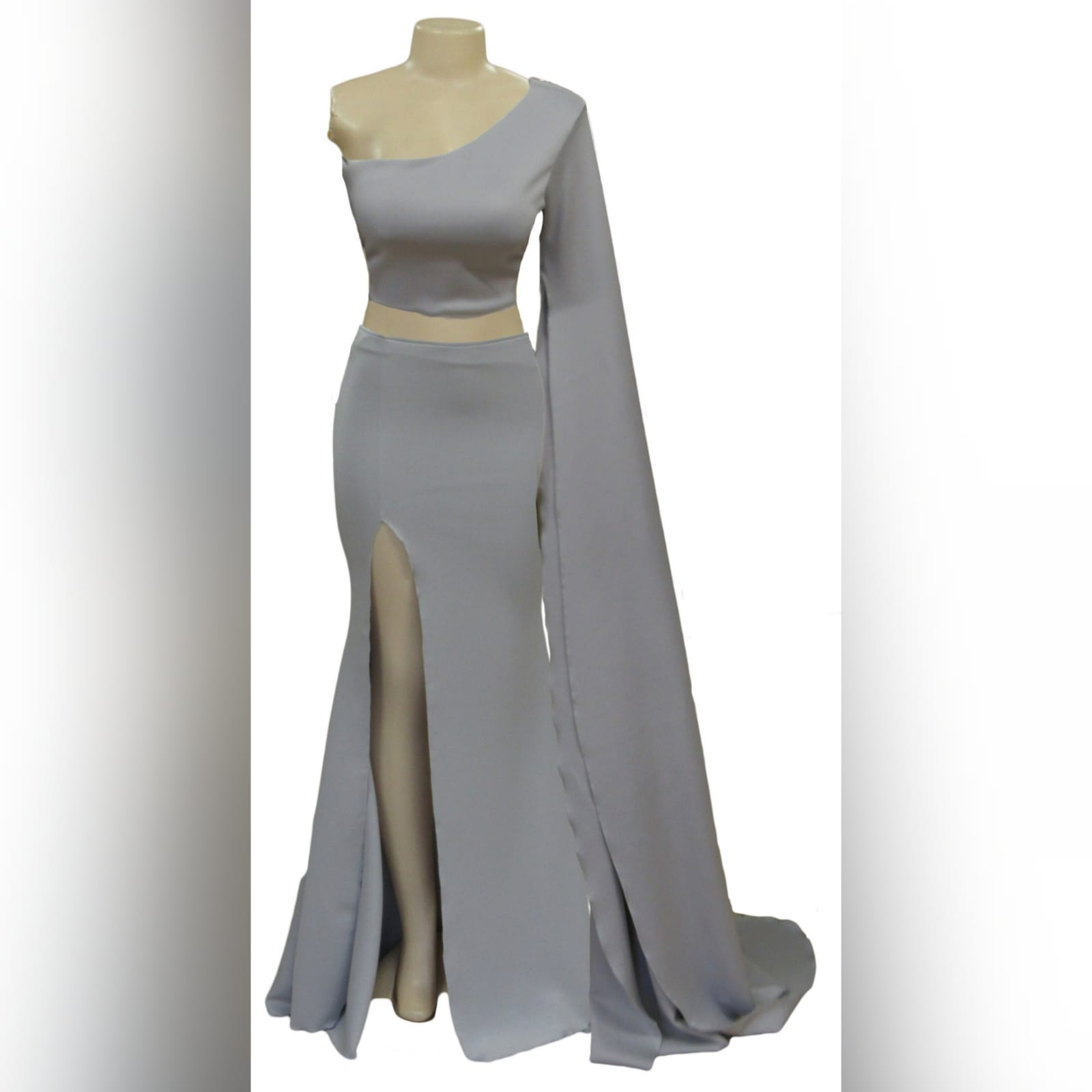 2 piece light grey prom dress 2 2 piece light grey prom dress, crop top with a single shoulder and a long wide sleeve creating a train. With a fitted long skirt, with a high slit.